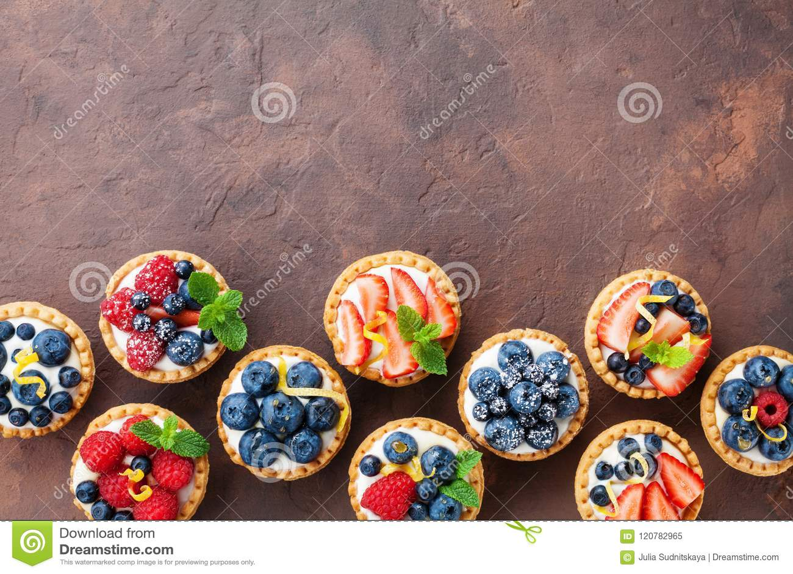 Köstliche Beere Tartlets oder Käse des Kuchens mit Sahne verzierten Zitronenschale und Minzenblatt von oben Geschmackvolle Gebäck