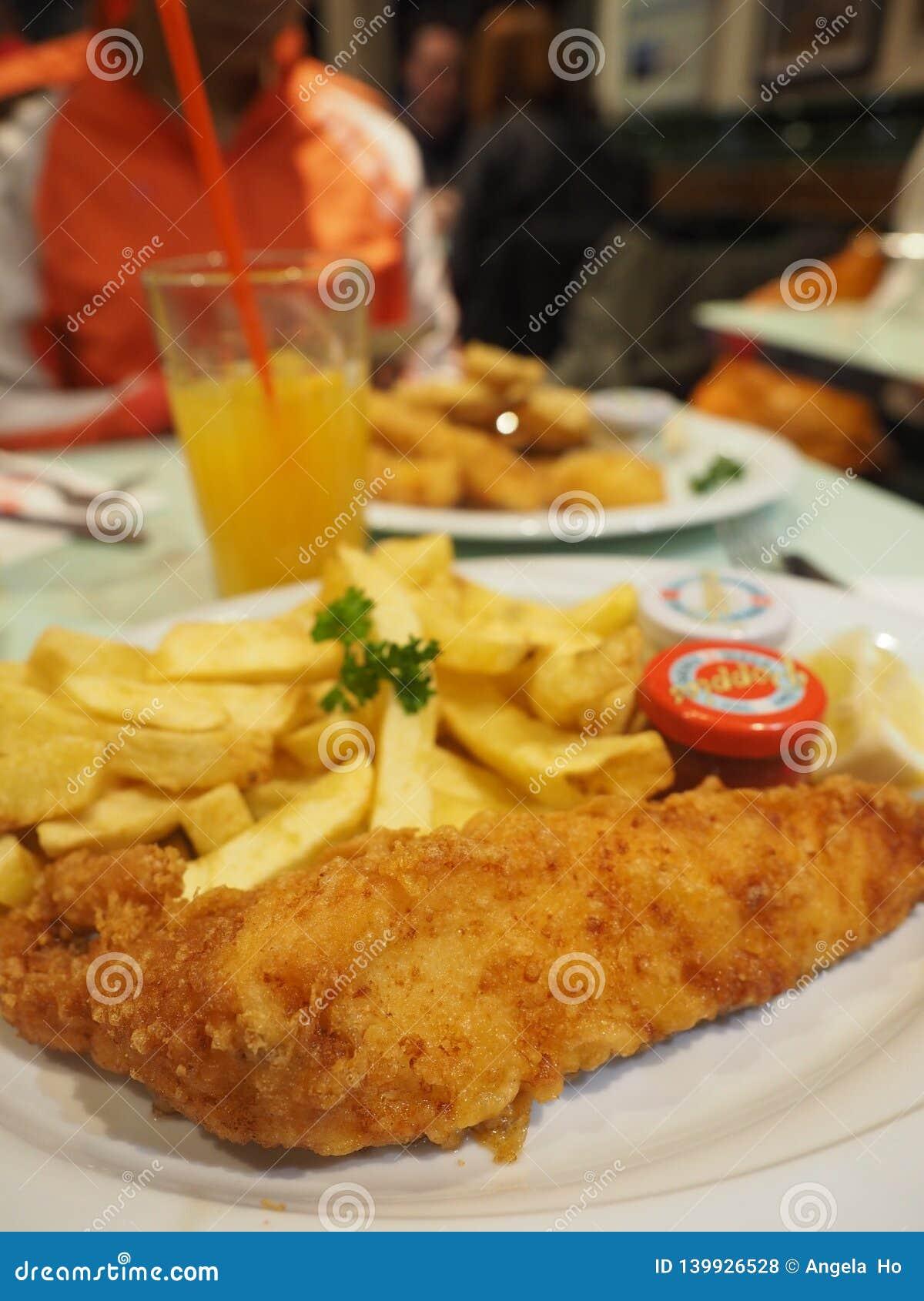 Köstliche gebratene Fisch und mit dem Glas Orangensaft bereit auf einer Platte
