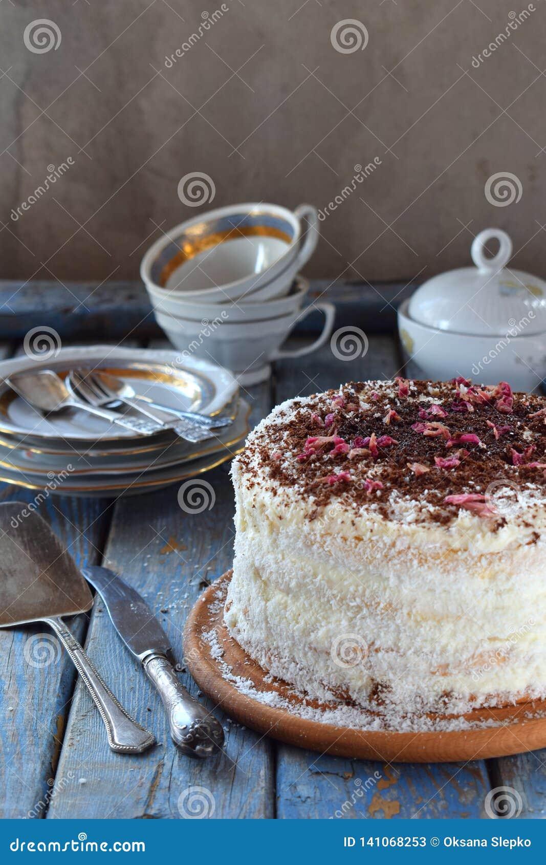 Köstliche Kokosnusstorte - Keks und Creme auf der Kokosnusscreme, verziert mit Schokoladenraspel und den kandierten rosafarbenen