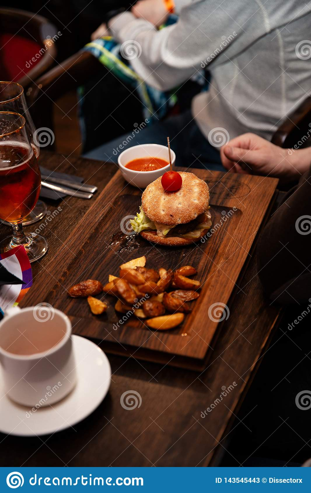 Köstlicher Burger mit Rindfleischpastetchen, Speck, Käse und Kohl auf rustikalem hölzernem Hintergrund diente in einer Stange