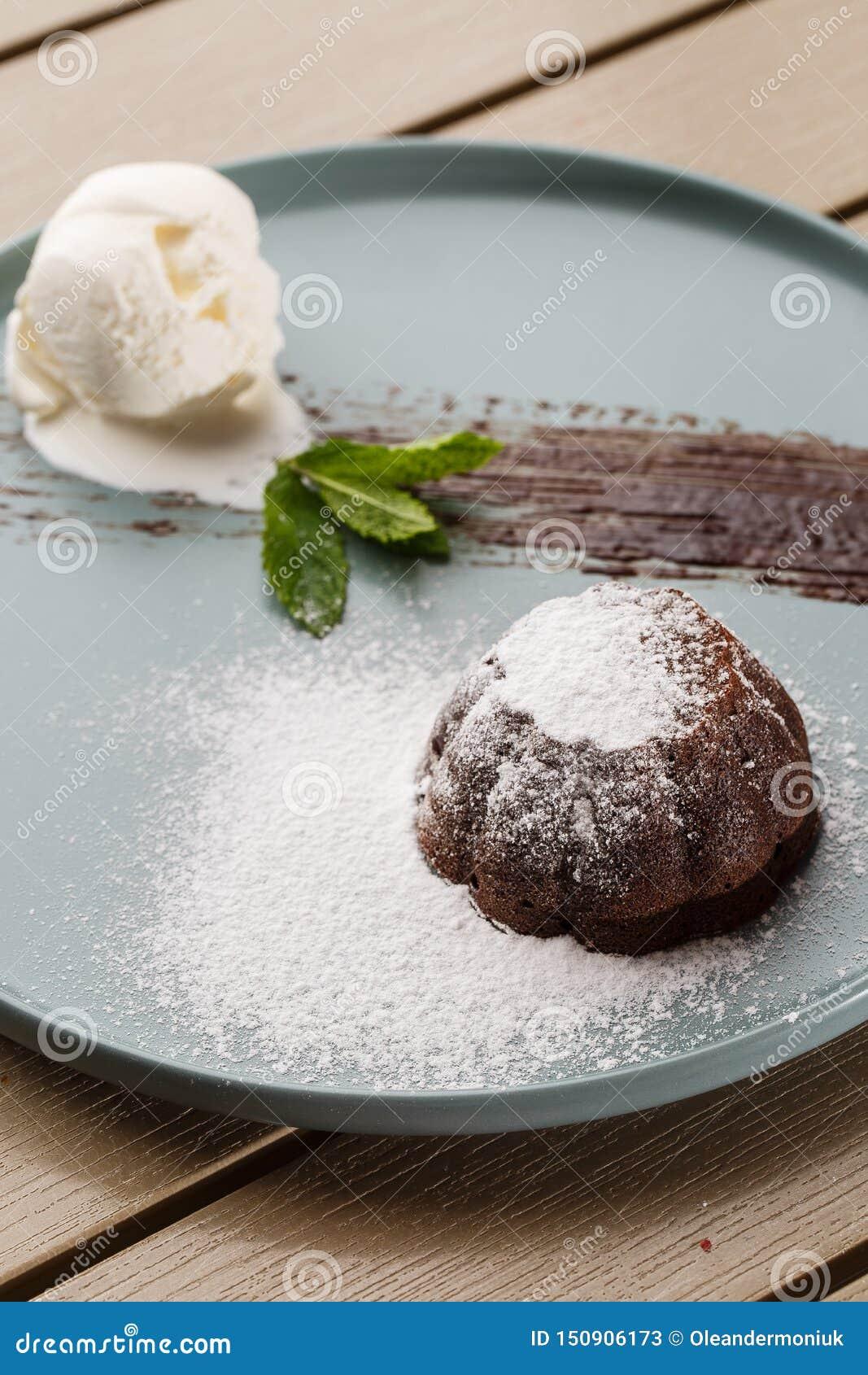 Köstlicher frischer Fondant mit heißer Schokolade und Eiscreme und Minze diente auf Platte Lavakuchenrezept H?lzerner Hintergrund