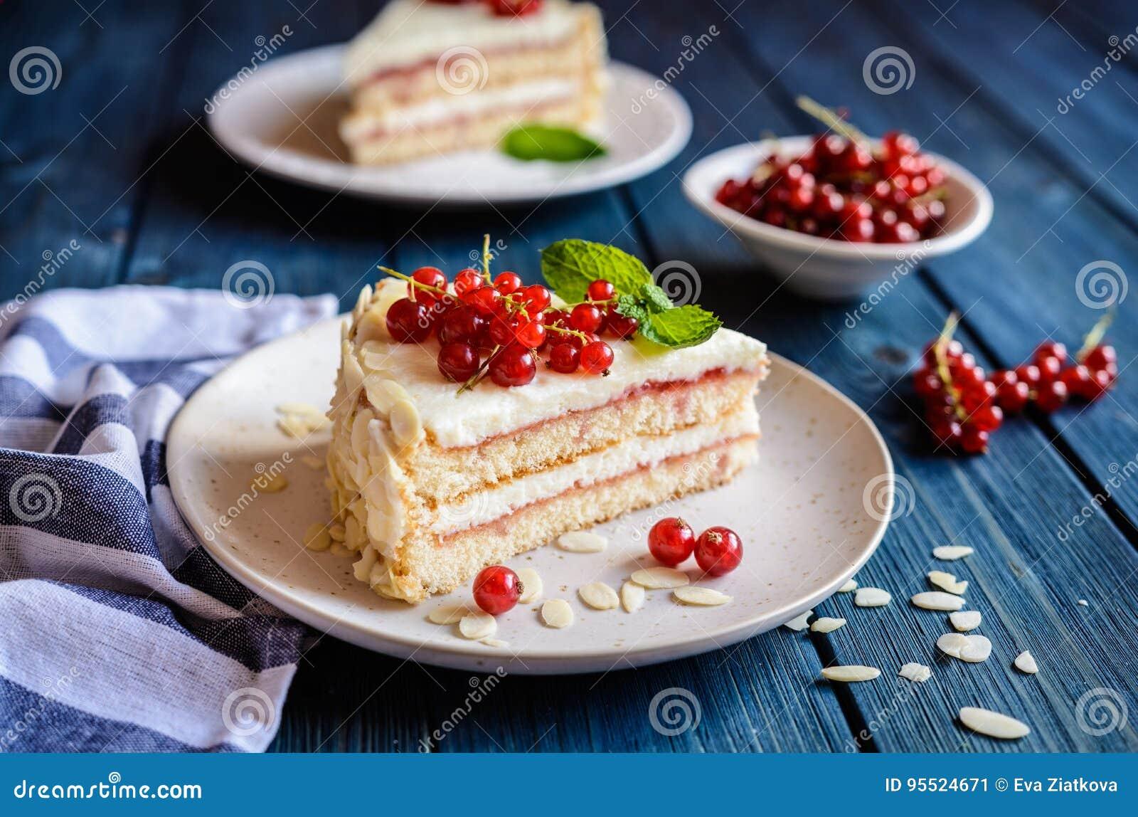 Köstlicher Kuchen mit mascarpone, Schlagsahne, roter Johannisbeere und Mandelscheiben