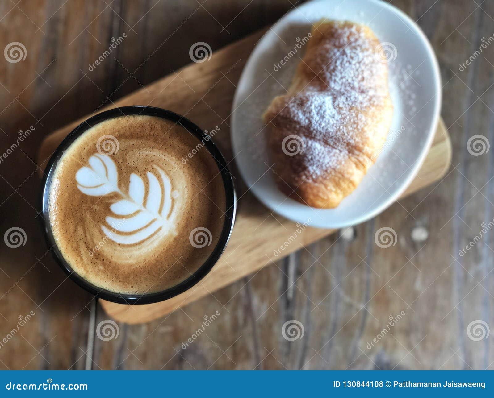 Köstliches Frühstück; Herzliebe Latte-Kunstkaffee in der schwarzen Schale und im Hörnchen überstieg mit Puderzucker