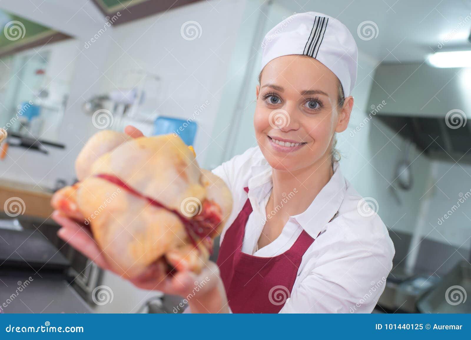 Kött för lycklig kvinnlig slaktare för stående bitande på slakträknaren