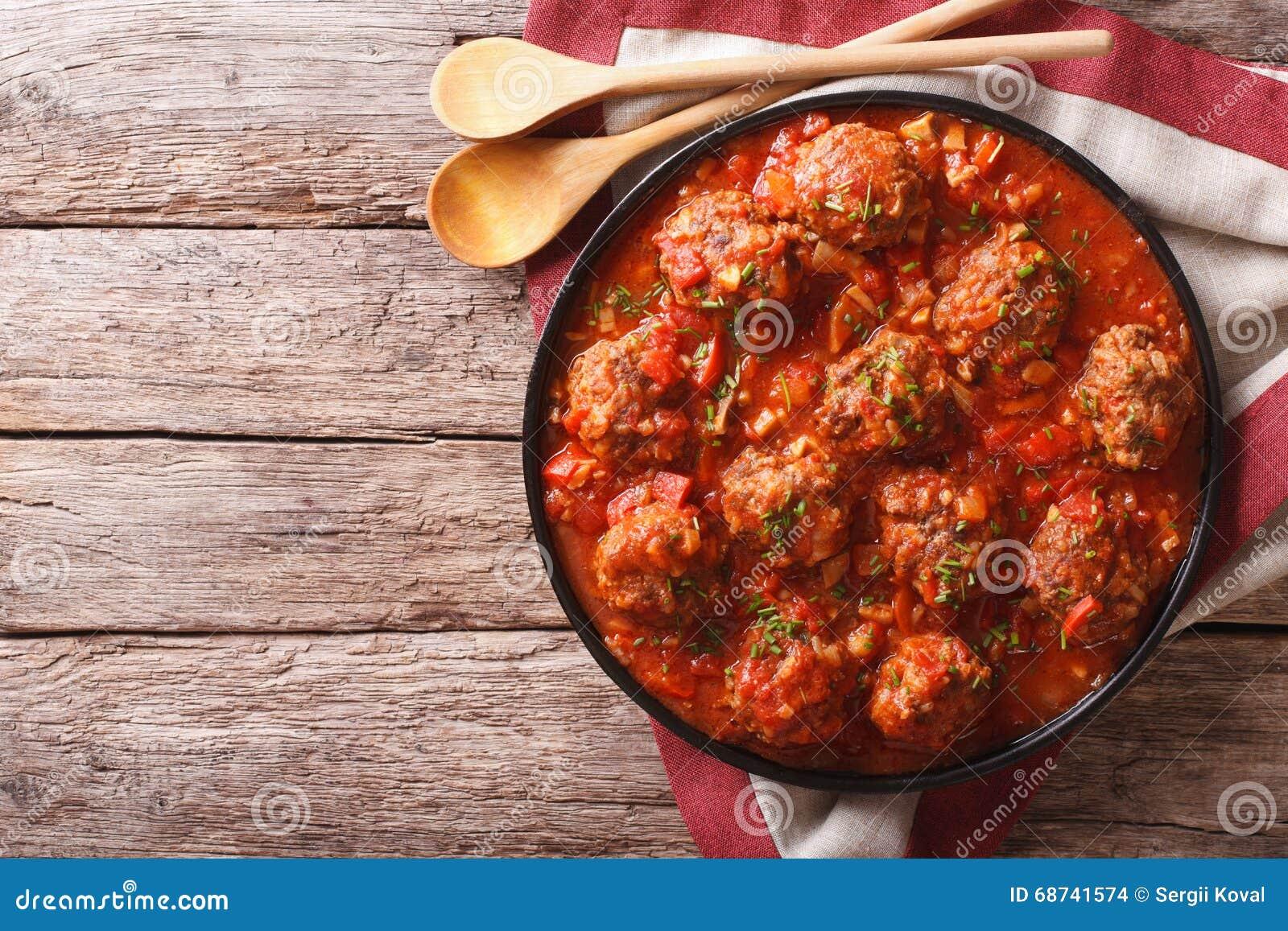 Köttbullar med kryddig tomatsås på en platta på tabellen Horiz