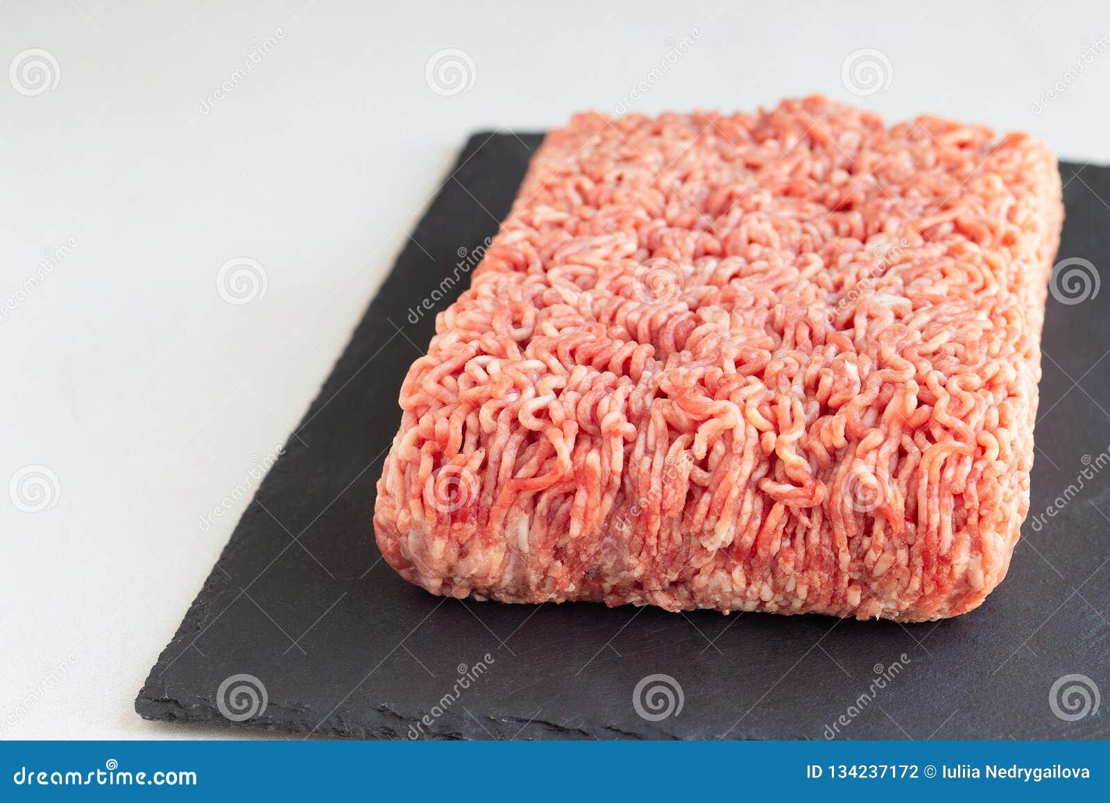 Köttfärs från griskött och nötkött, jordkött på mörker kritiserar brädet som är horisontal, kopieringsutrymme
