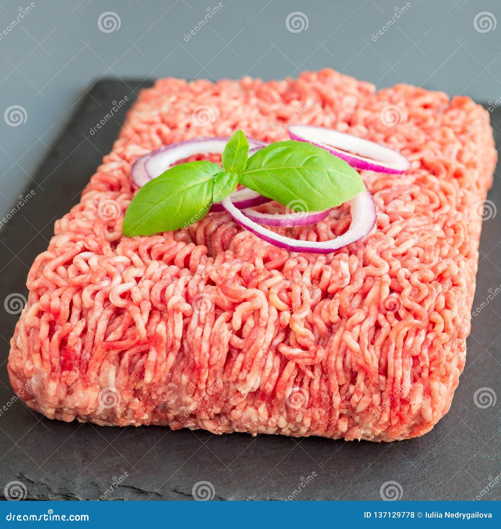 Köttfärs från griskött och nötkött Malt kött med ingredienser för att laga mat på mörker kritiserar brädet, fyrkantigt format