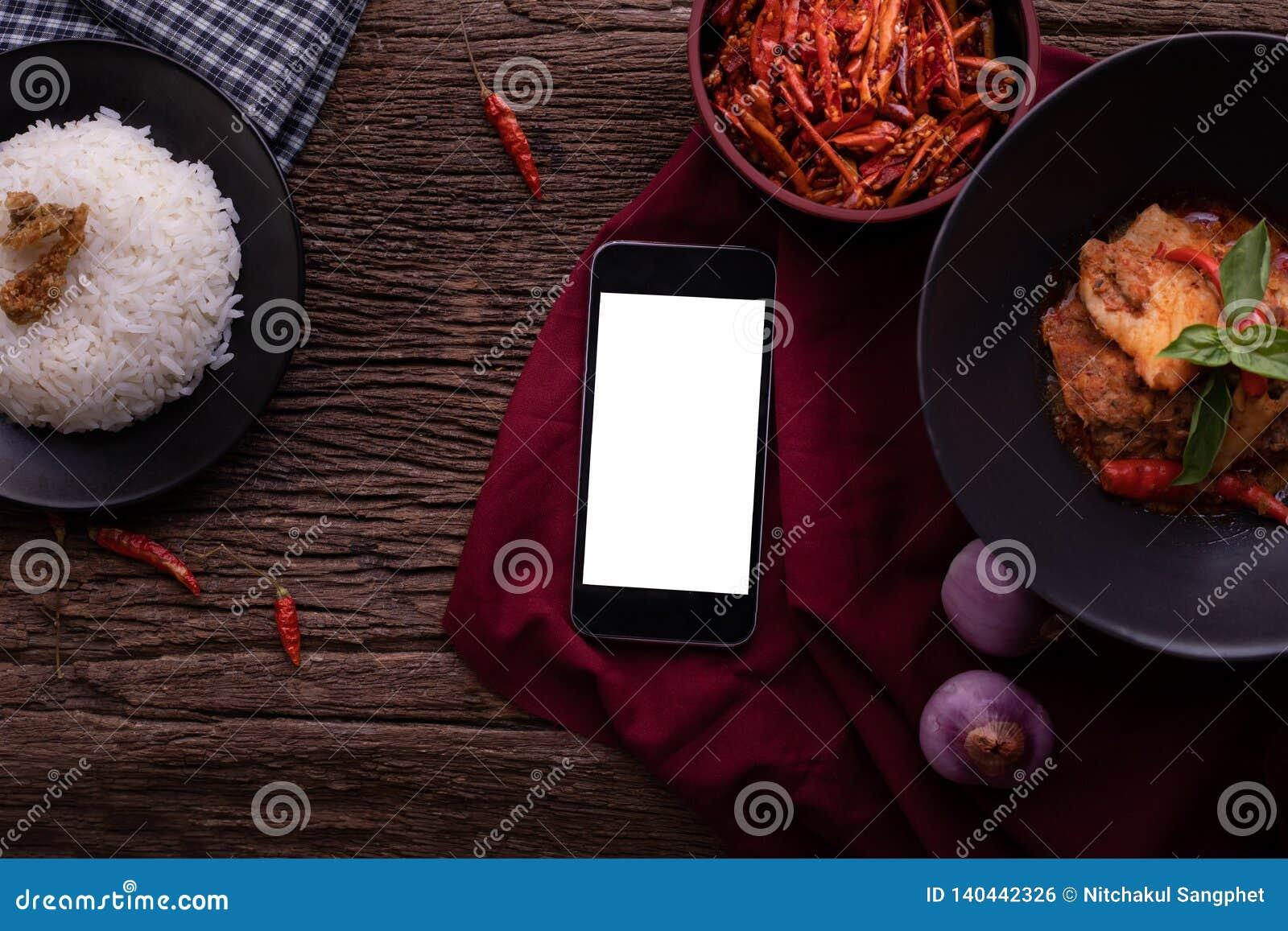 Küchentisch mit leerem Bildschirm auf intelligentem Telefon, Tablette, Handy und getrocknetem rotem Schweinefleischkokosnusscurry