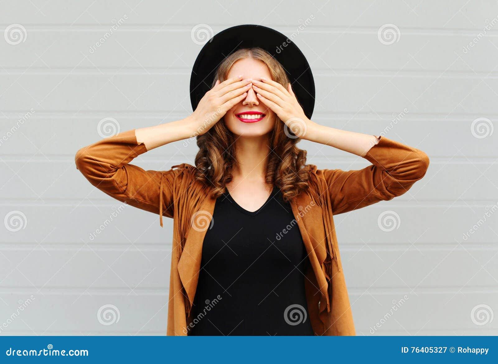Kühle junge Frau der Mode recht schließt das nette Lächeln der Augen, eine Hut-Braunjacke der Weinlese tragend elegante, die Spaß