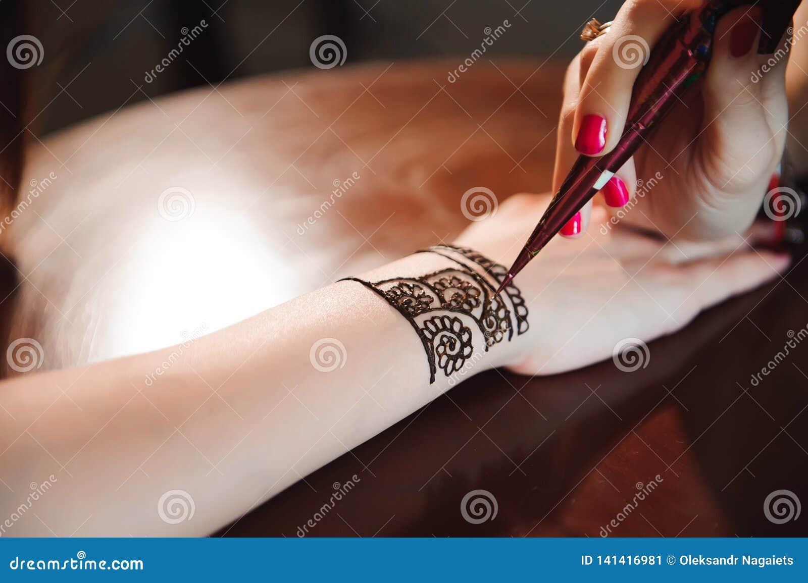 Künstler, der Hennastrauchtätowierung auf Frauenhänden anwendet Mehndi ist traditionelle indische dekorative Kunst