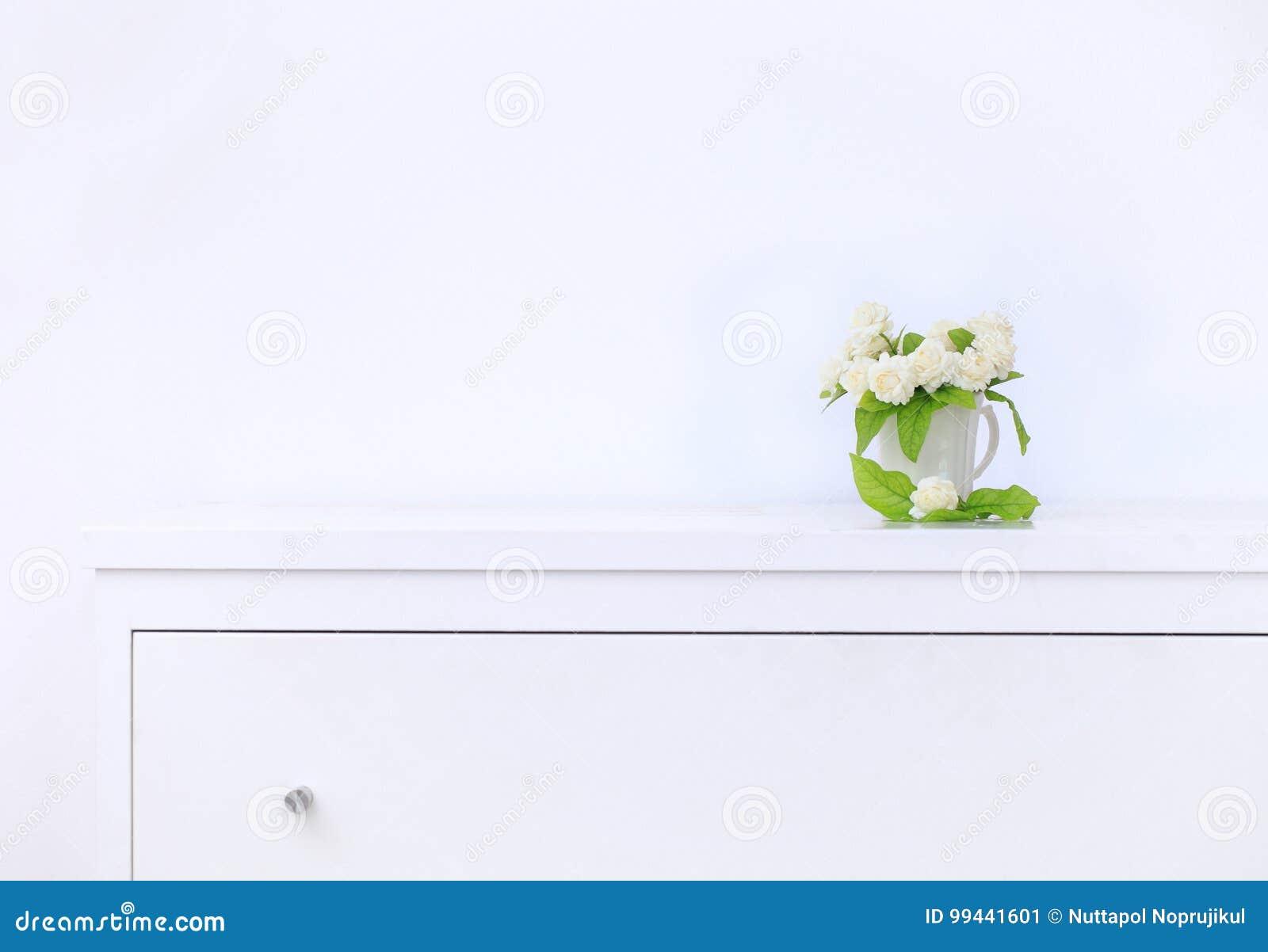 Künstliche Jasminblume im Topf am weißen Tisch mit