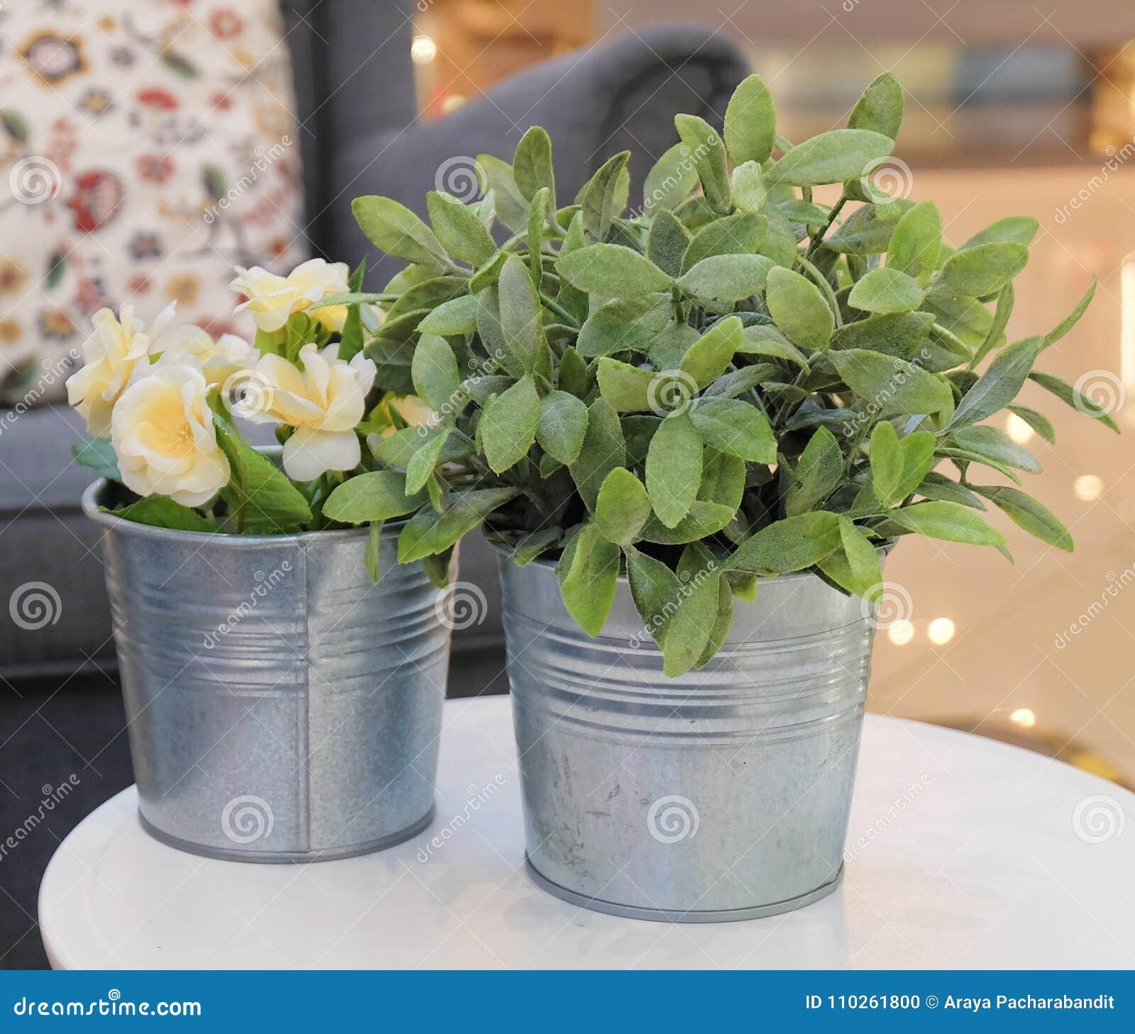 Künstliche Rosen und Grünpflanzen in den Metalltöpfen