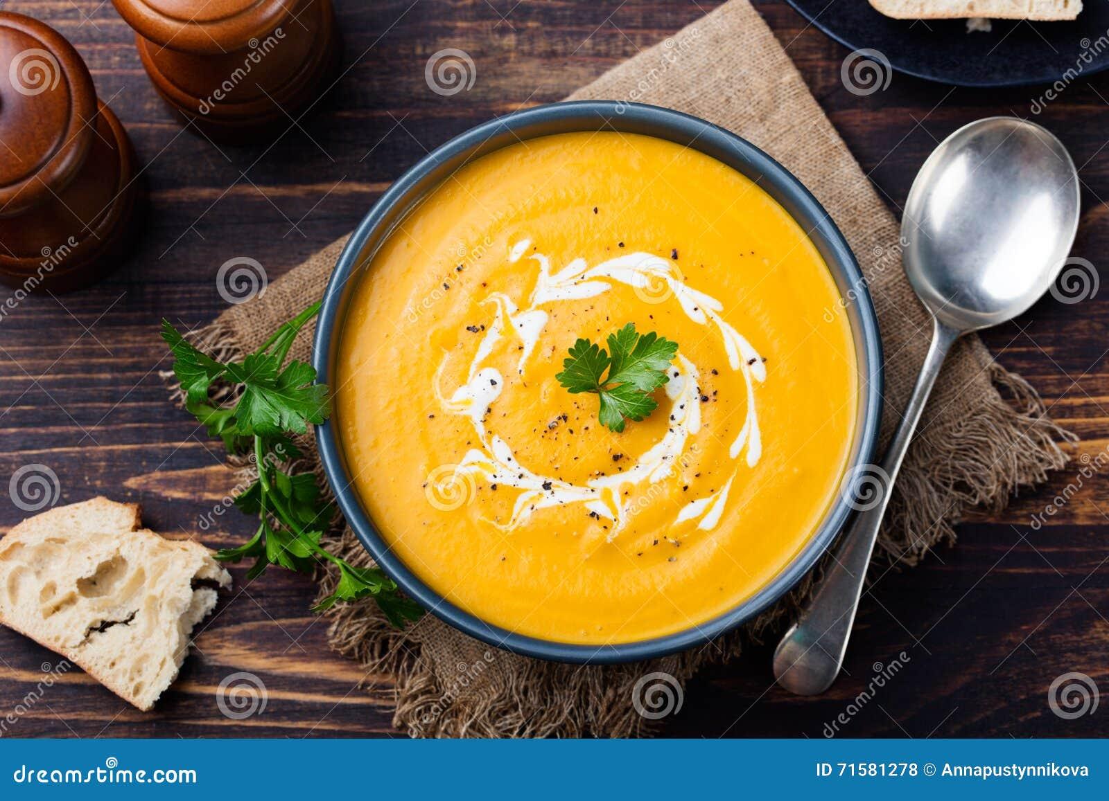 Kürbis- und Karottensuppe mit Sahne und Petersilie auf Draufsicht des dunklen hölzernen Hintergrundes