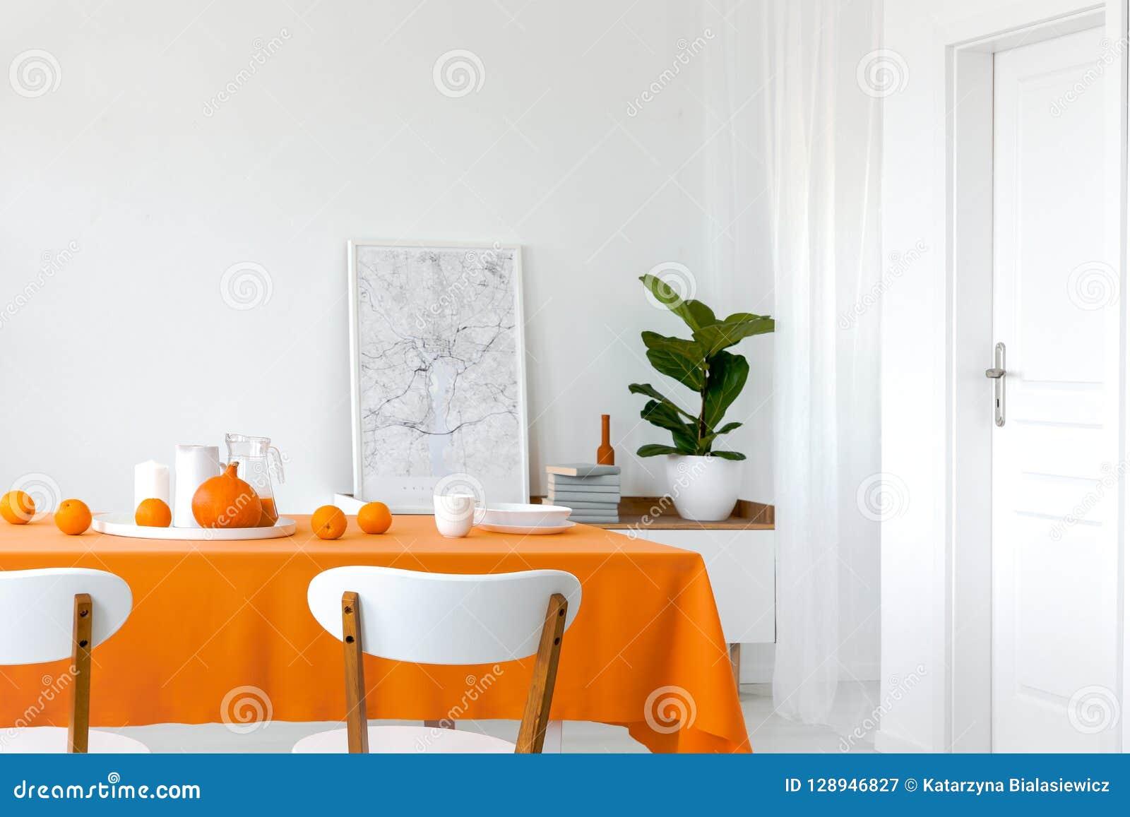 Kürbis und Orangen auf dem Esszimmertisch, gestaltete Karte nahe bei Stapel von Büchern im Regal