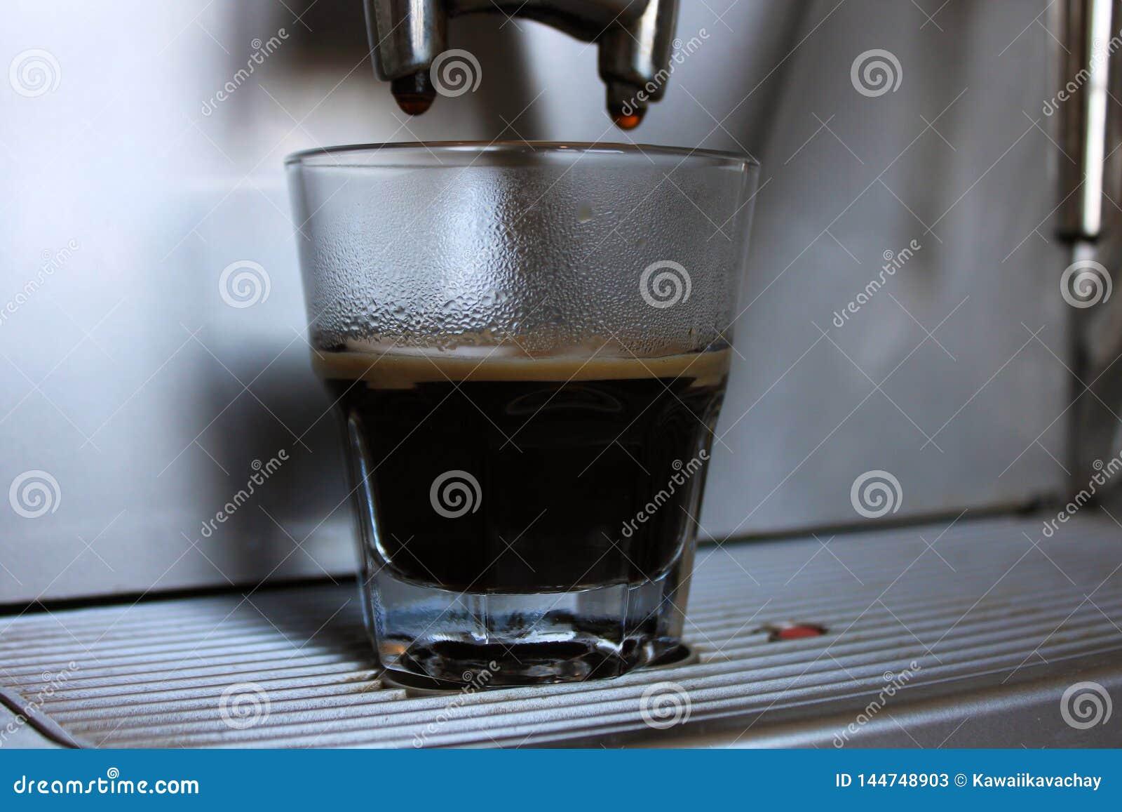 Kürzlich gemachter Espresso mit einem Schaum auf der Maschine in der Kaffeestube oder im Café