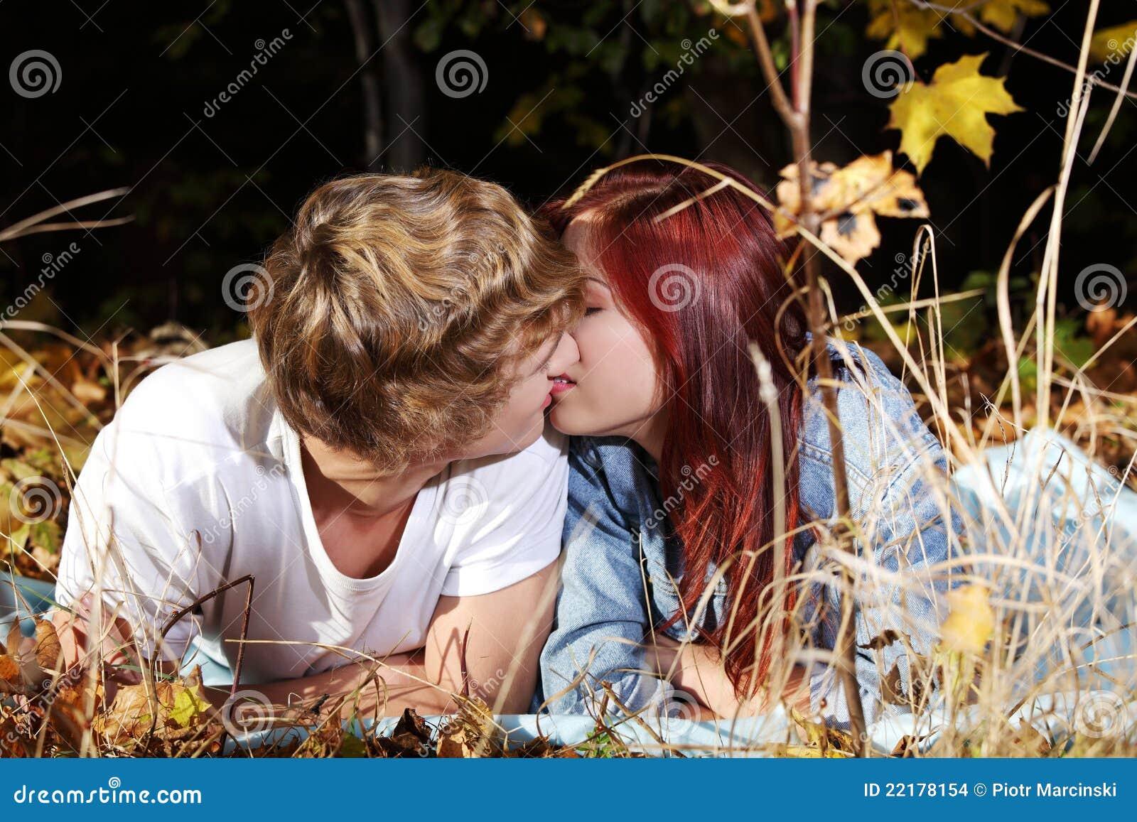Küssende paare des jungen kaukasiers die auf wiese draußen liegen