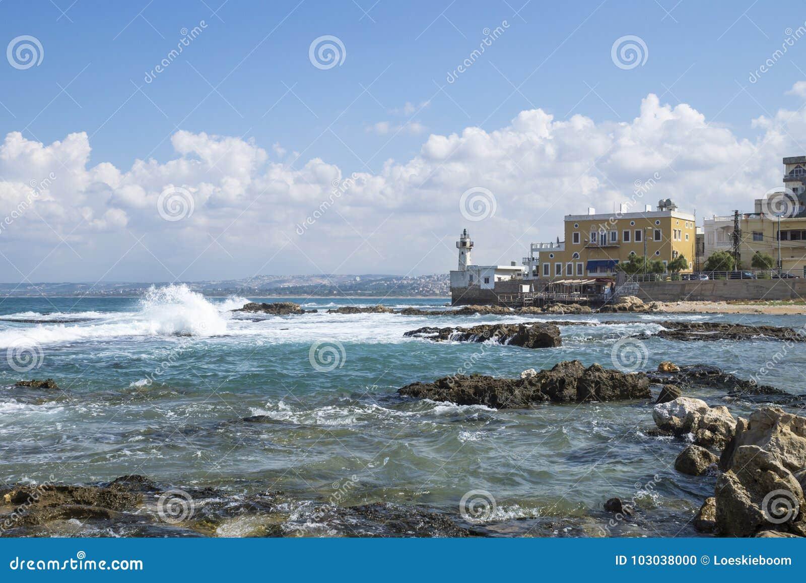 Küstenlinie im Reifen in dem Ozean mit Wellen und mit Leuchtturm im Reifen, sauer, der Libanon