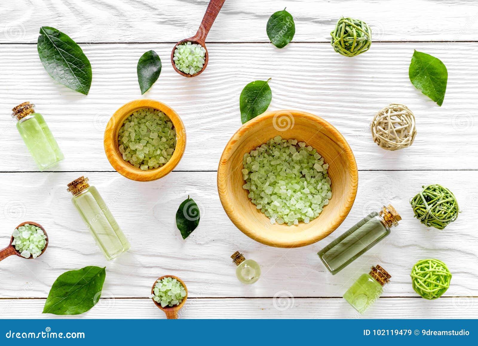 Kąpielowa sól w ziołowy kosmetycznym ustawiającym z herbacianą oliwką opuszcza na białym drewnianym tło odgórnego widoku wzorze