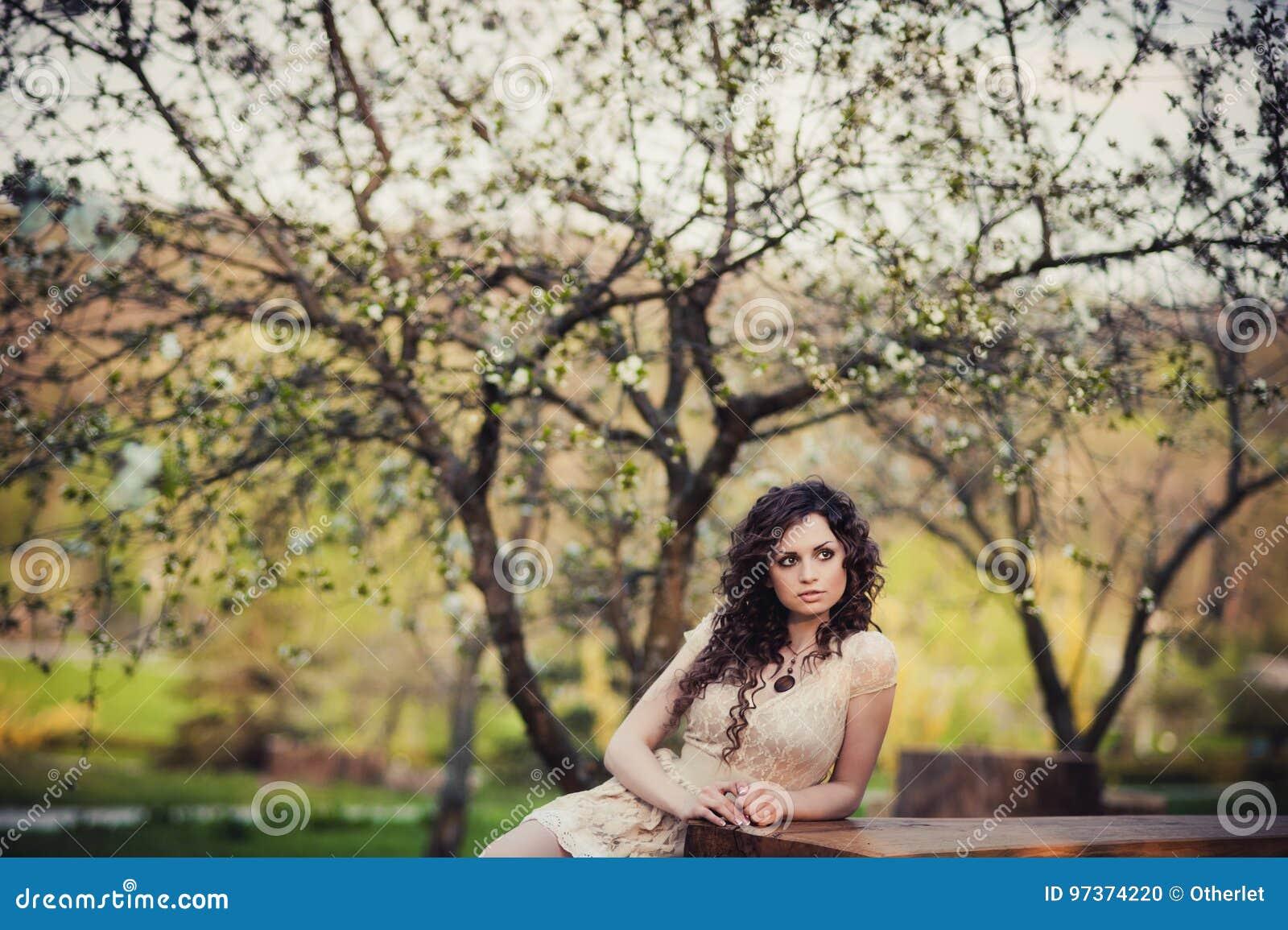 Kędzierzawa brunetki dziewczyny pozycja w kwitnąć drzewa