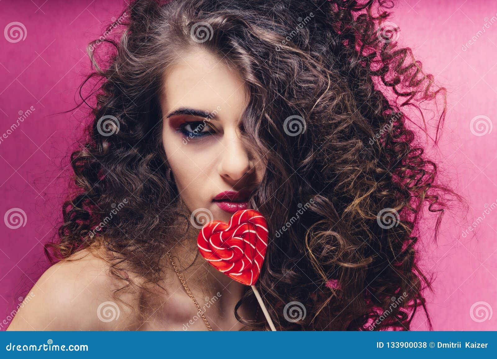 Kędzierzawa piękna dziewczyna z czerwonym kierowym lizakiem na różowym tle
