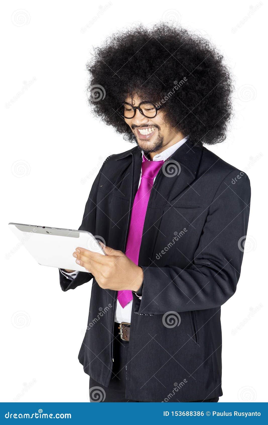 Kędzierzawego włosy biznesmen używa pastylkę na studiu