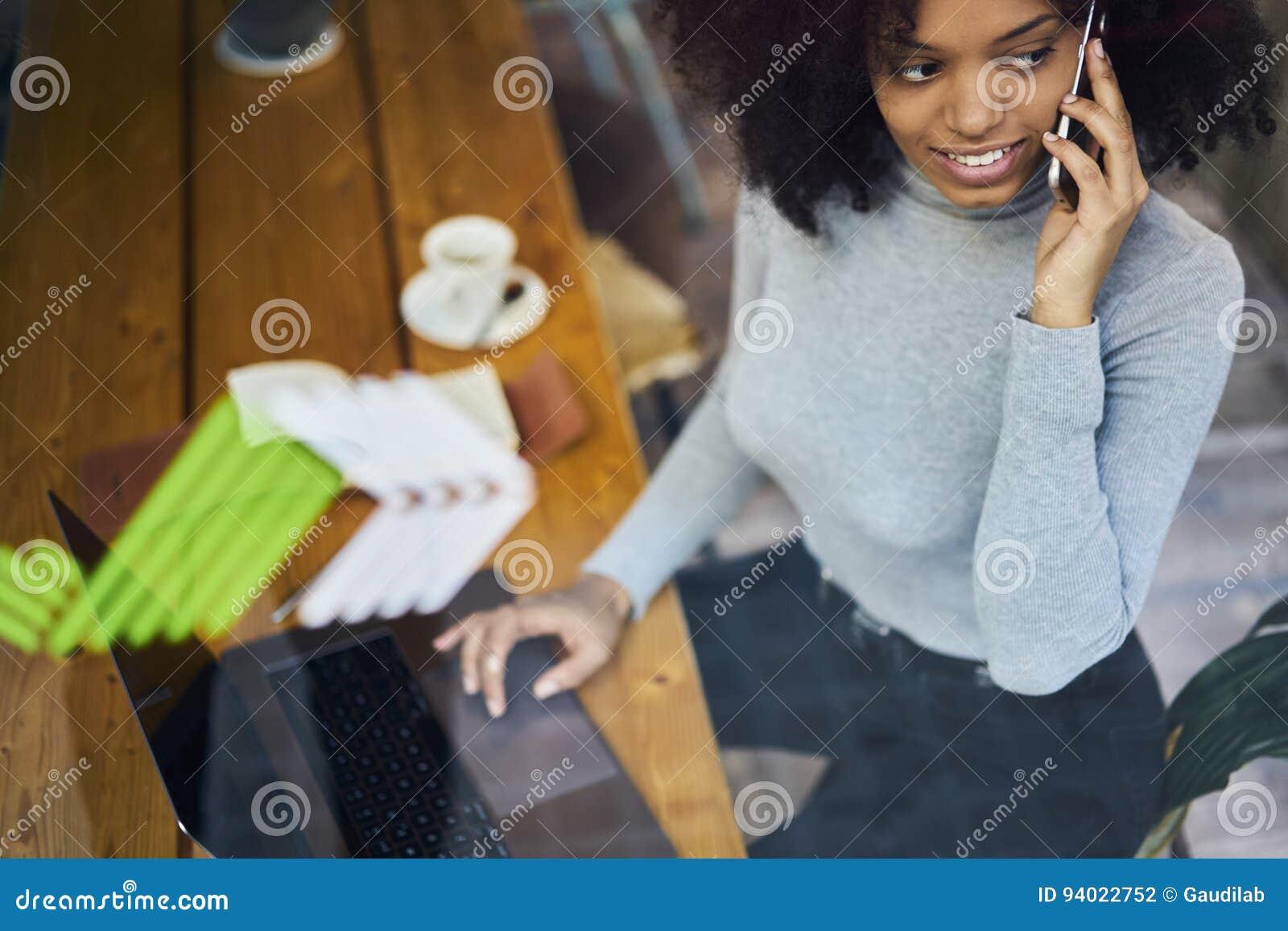 Kędzierzawy afroamerykanin w szarej kurtce używać bezprzewodowego związek sieć