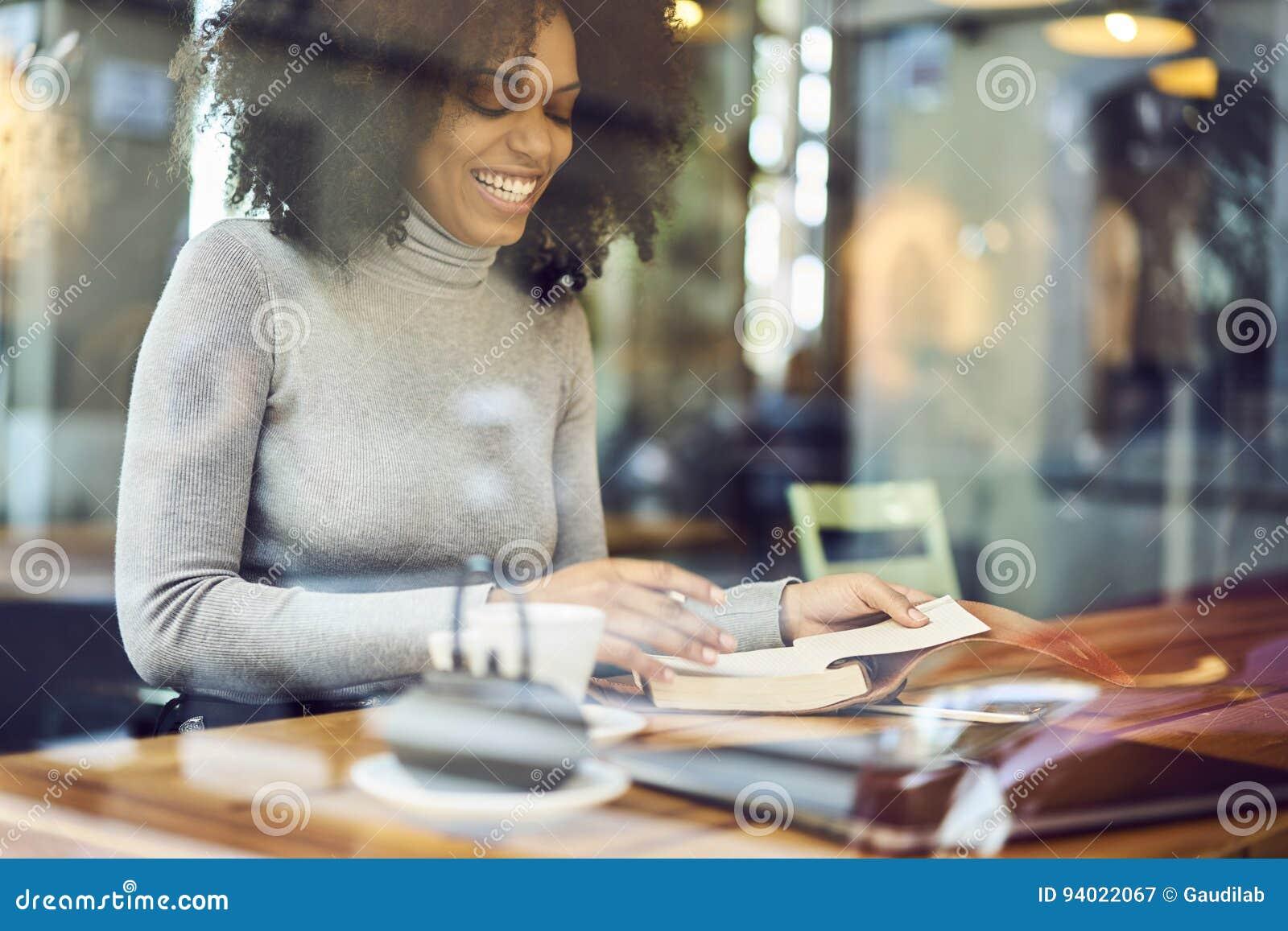 Kędzierzawy afroamerykanin w szarym kurtki obsiadaniu przy stołowym pobliskim okno w nowożytnym sklep z kawą