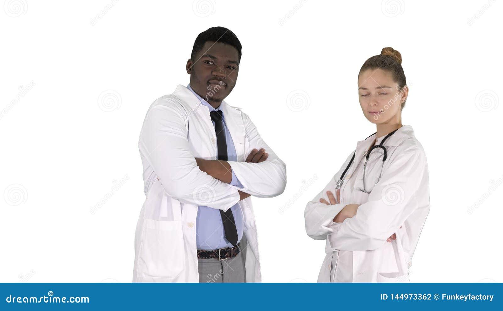 Γιατροί γυναικών και ανδρών με τα διασχισμένα όπλα στο άσπρο υπόβαθρο
