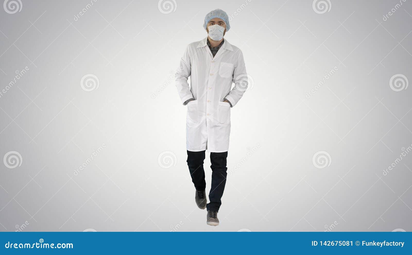 Идя молодой мужской доктор нося хирургическую маску на предпосылке градиента