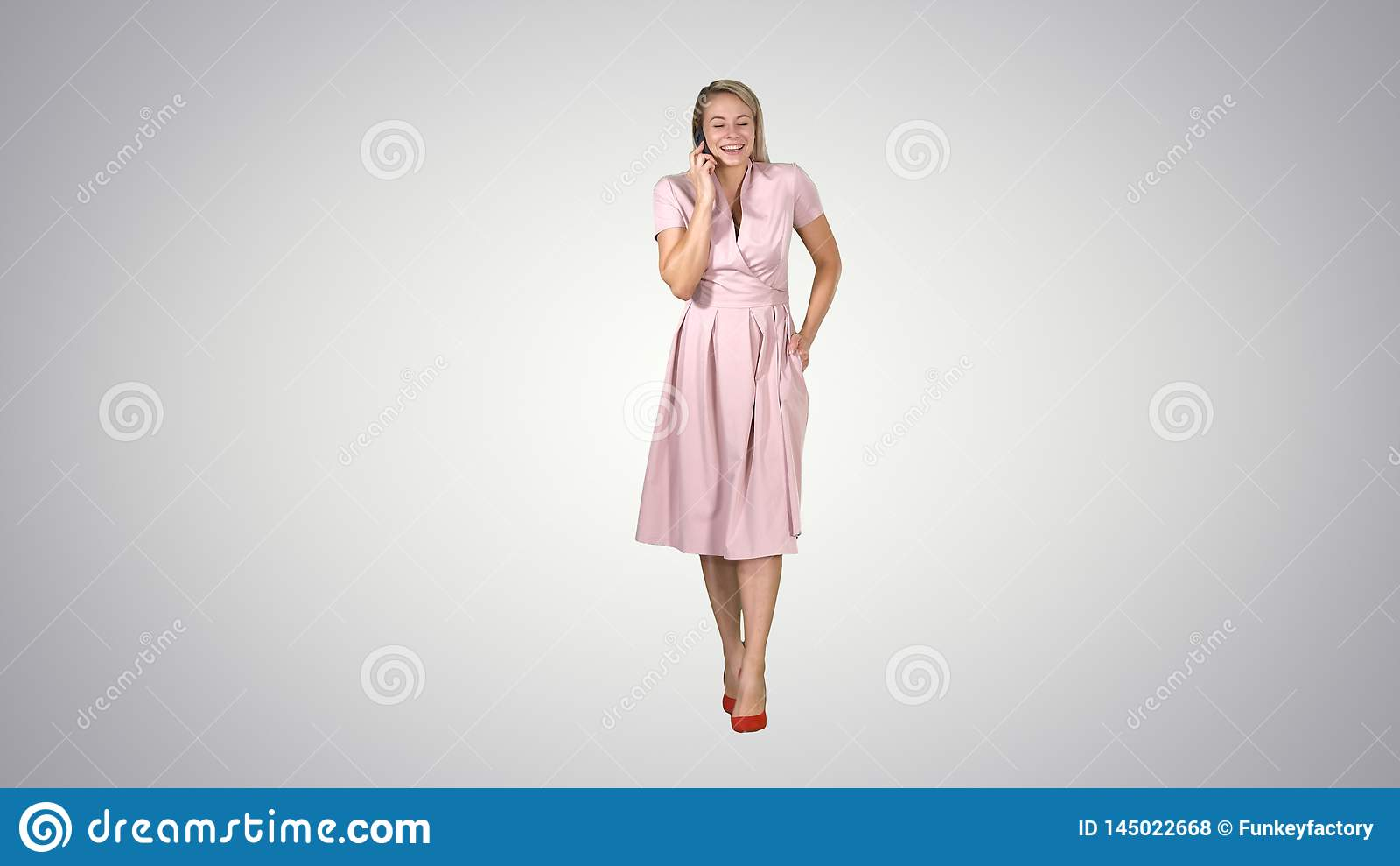 Счастливая усмехаясь женщина говоря на сотовом телефоне пока идущ на предпосылку градиента