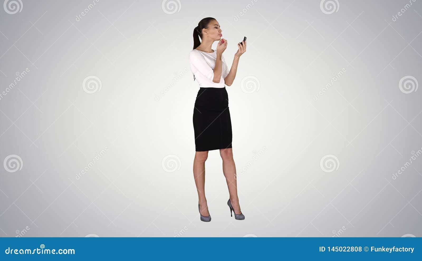美女,洗染她的嘴唇唇膏桃红色,看在梯度背景的镜子