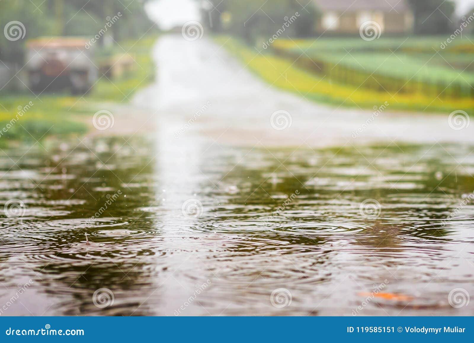 Kałuża z wodą na drodze podczas prysznic Silny deszcz dalej
