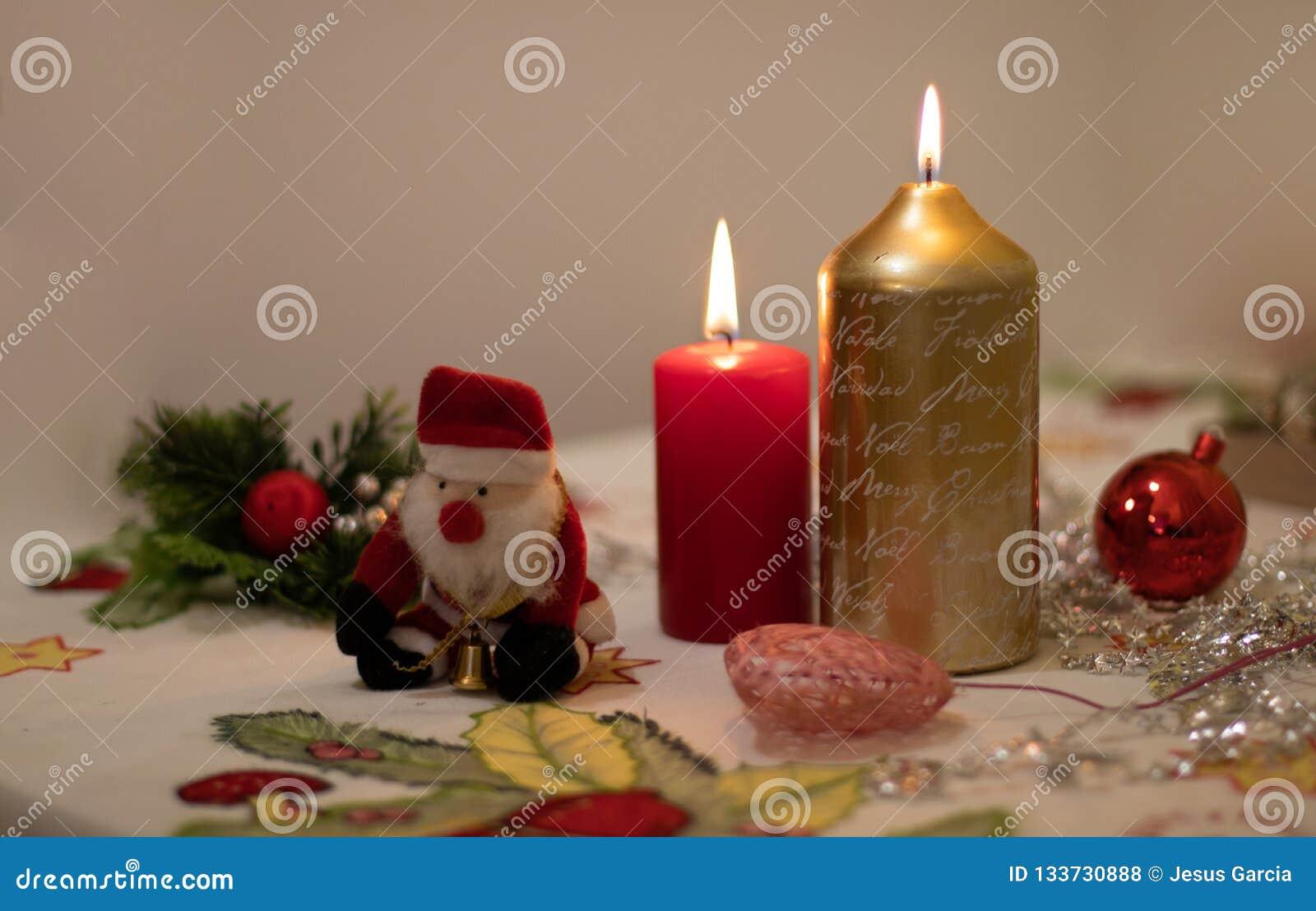 Kaarsen met Kerstmisdecoratie en een Santa Claus-pop op een tafelkleed worden aangestoken dat