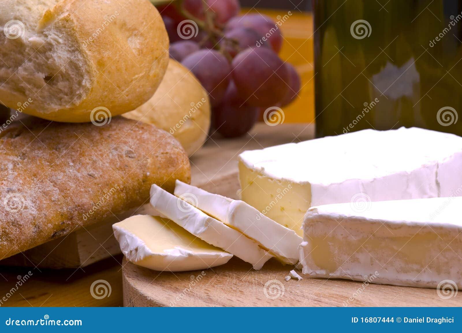 Kaas, brood, druiven en wijn op houten lijst