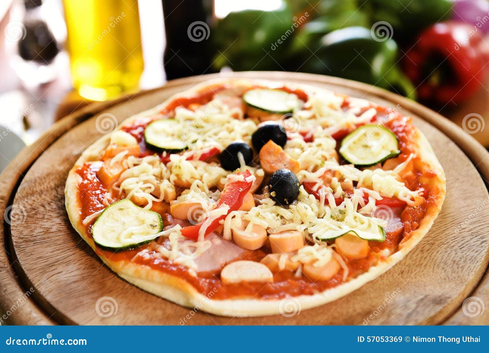 Kaas op een vers voorbereide pizza op houten raad