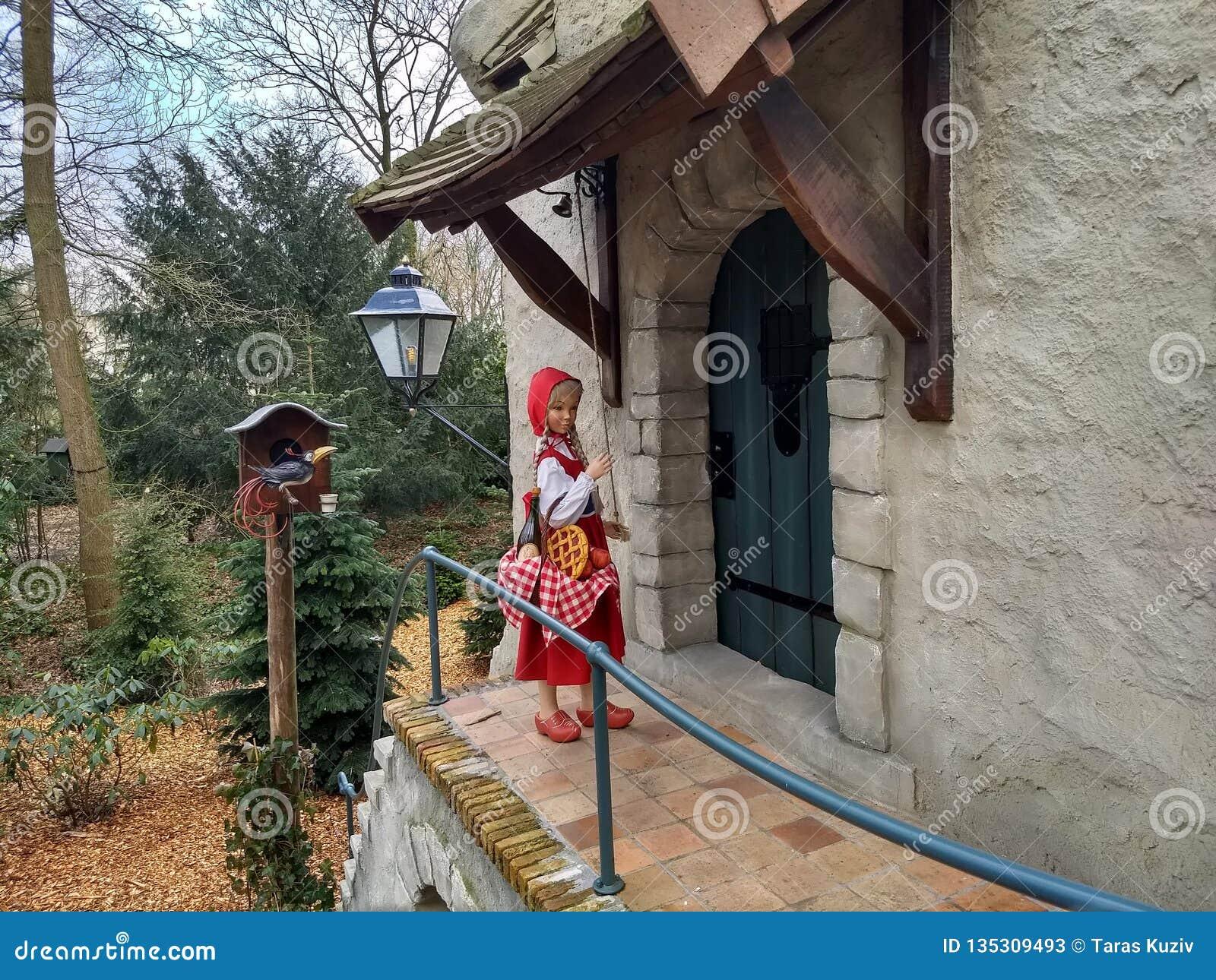Kaatsheuvel/Países Baixos - 29 de março de 2018: Pouco capa vermelha perto da porta de uma casa no parque temático Efteling