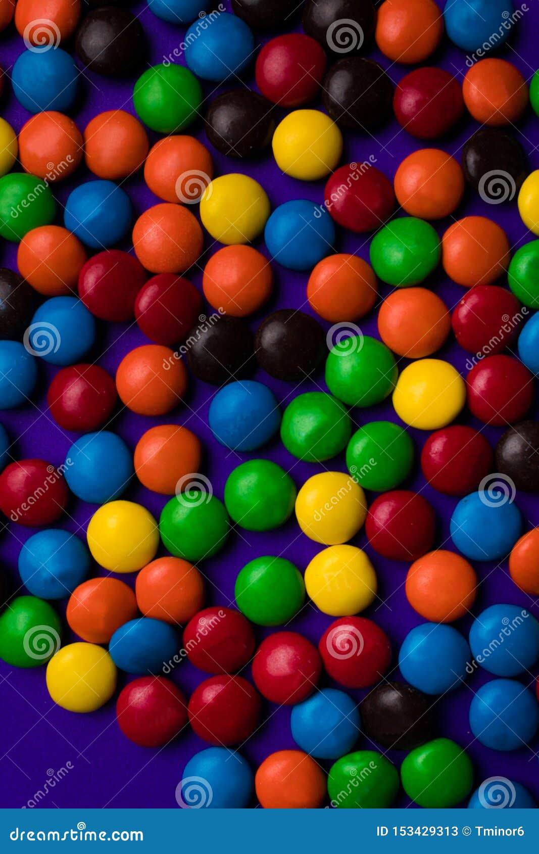 Kader van veelkleurig suikergoed met een beschikbare ruimte op een purpere achtergrond