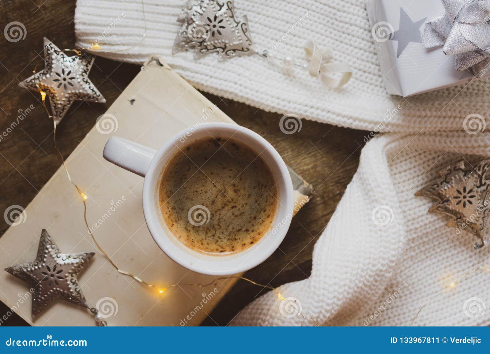 Kaffe bok, försilvrar julgåvan och garneringar på en träbakgrund