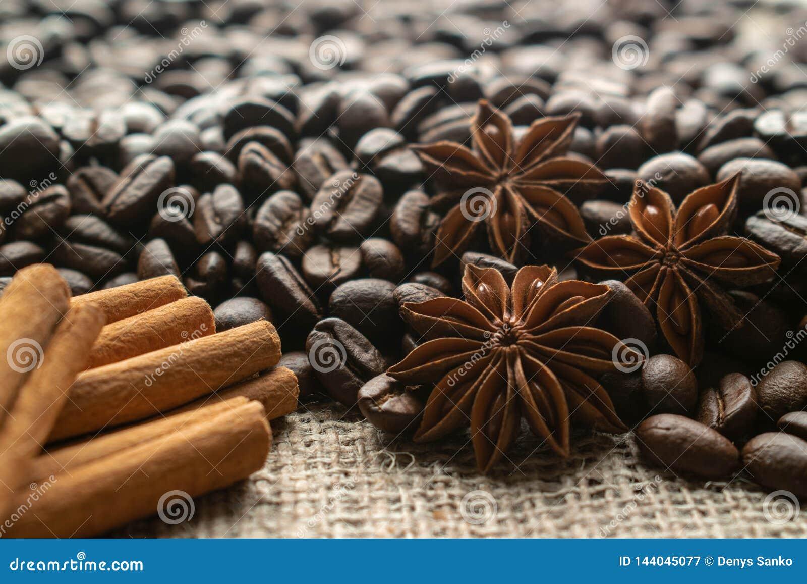Kaffe för hel böna med stjärnaaniseas och kanelbruna pinnar på ljus säckväv