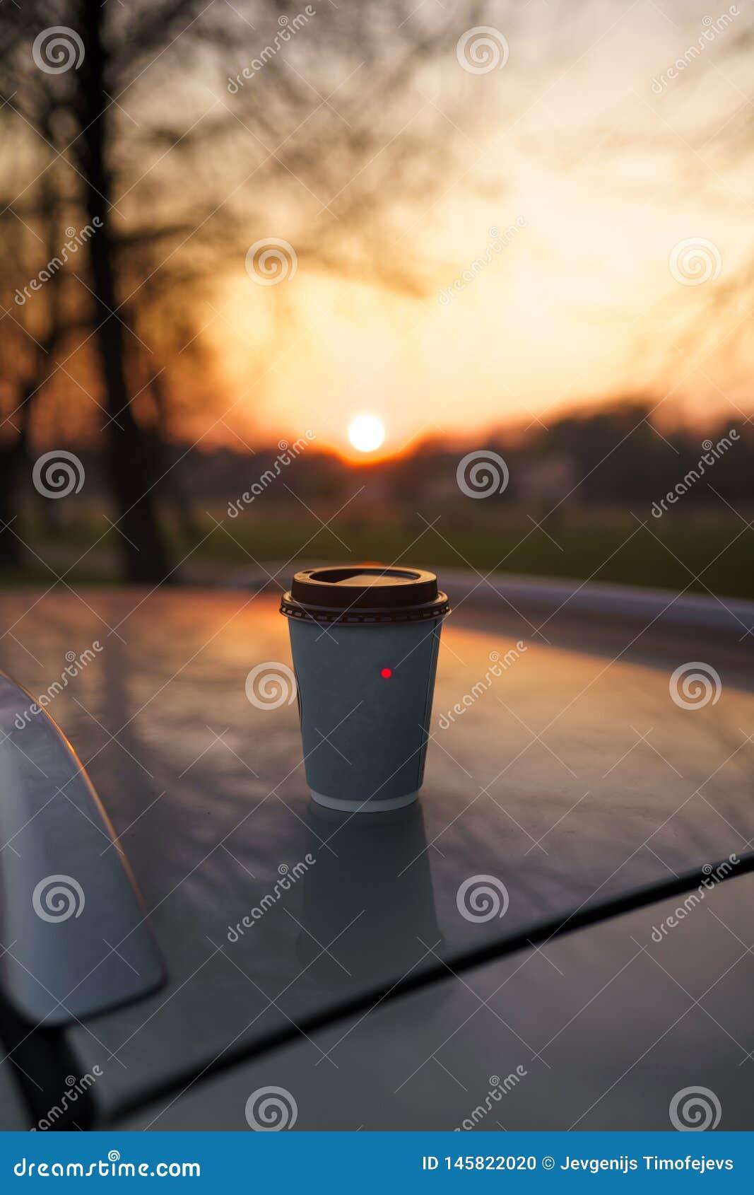 Kaffe för pappers- kopp på solnedgången som står på ett biltak med härligt ut ur fokusbokeh