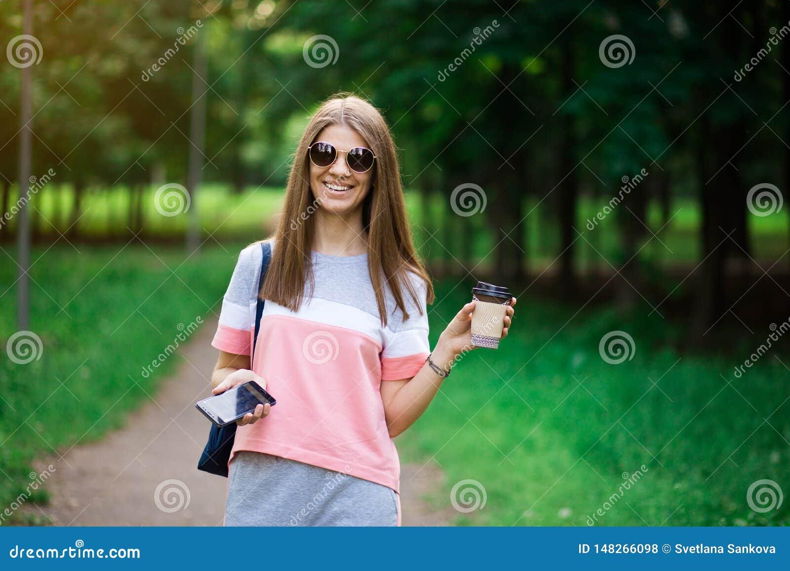 Kaffe går på Härlig ung kvinna i solglasögon som rymmer kaffekoppen och ler, medan gå gatan
