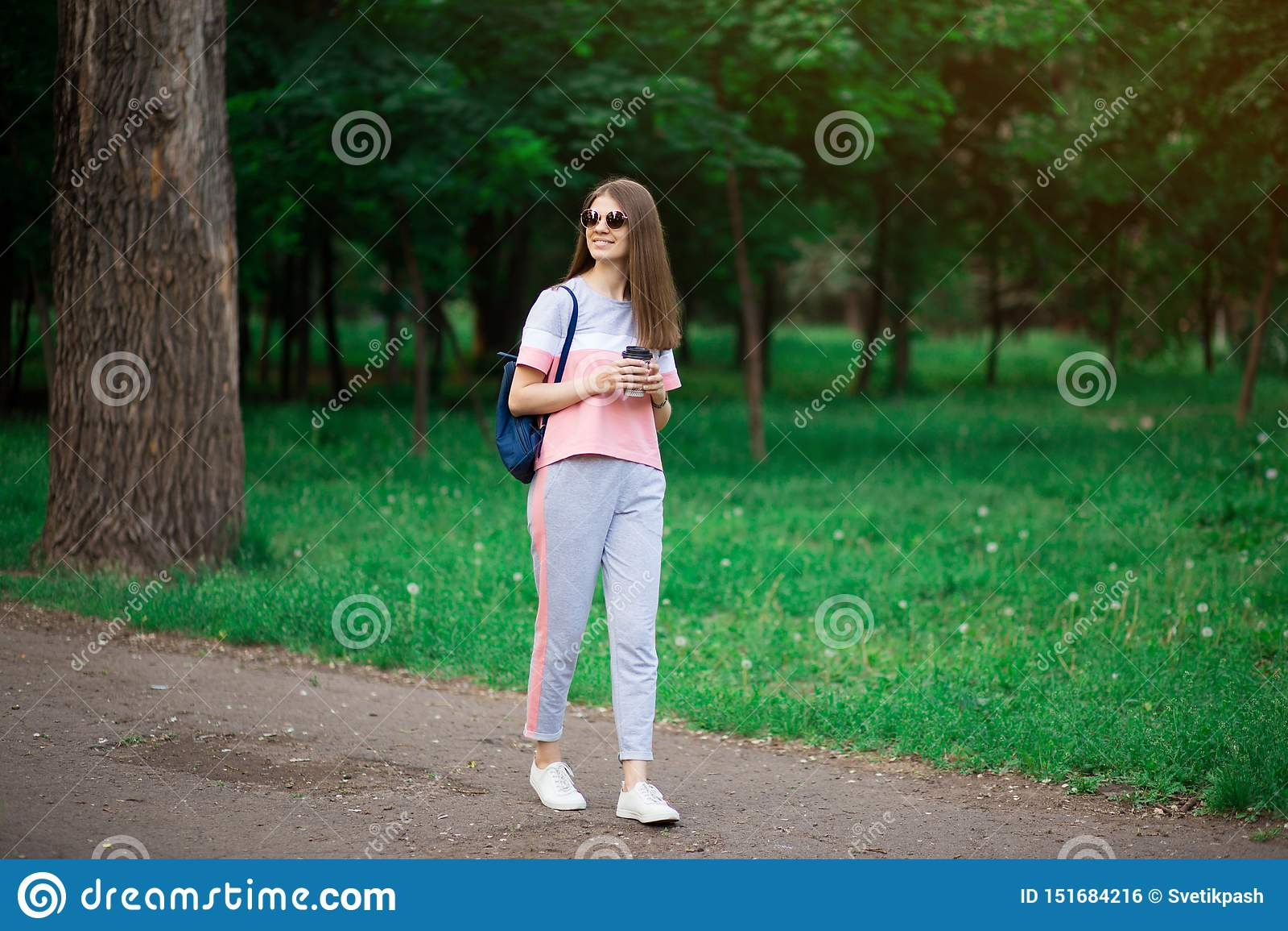 Kaffe g?r p? Härlig ung kvinna i solglasögon som rymmer kaffekoppen och ler, medan gå