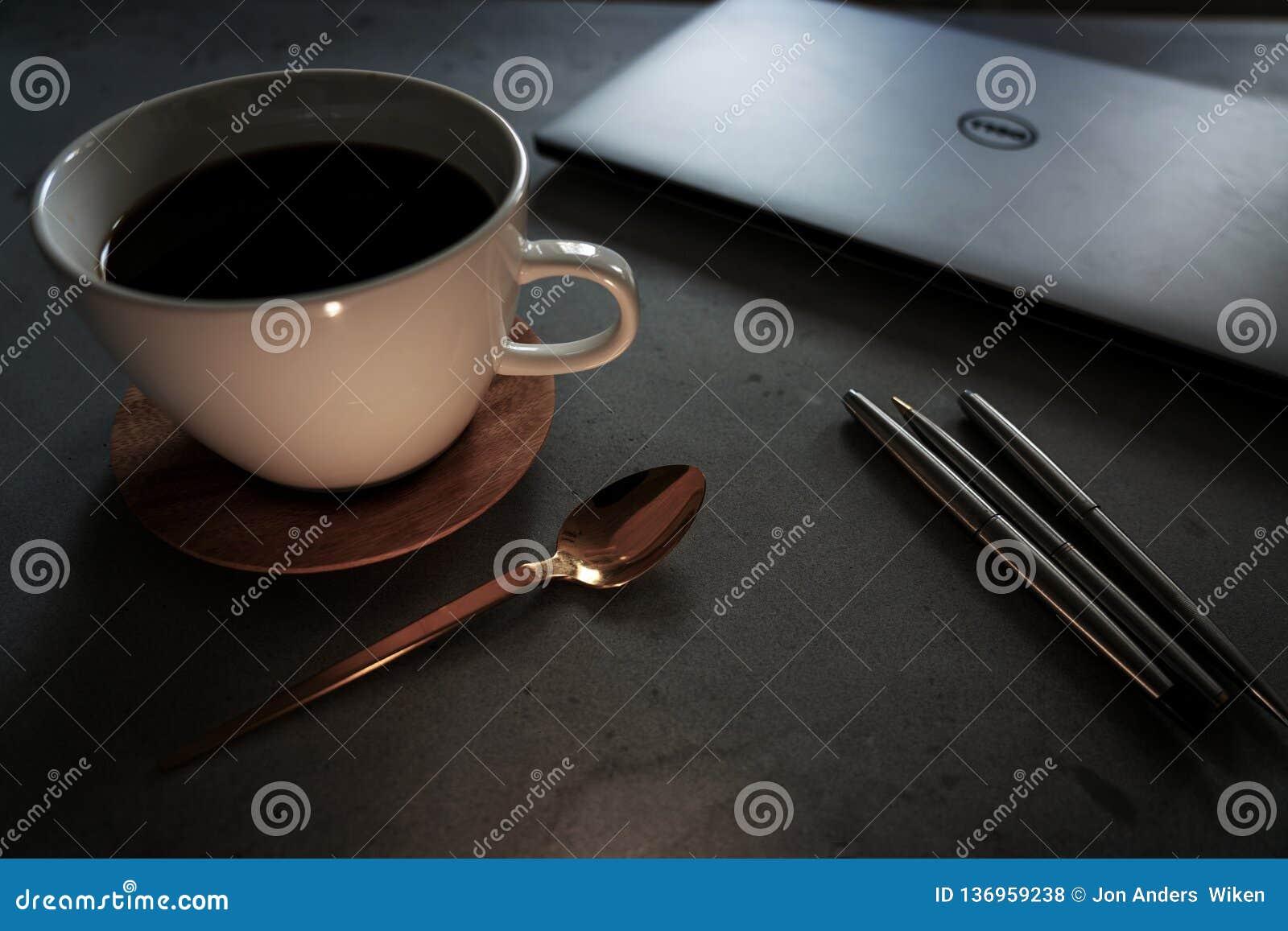 Kaffe med bärbara datorn och pennor på den konkreta tabellen