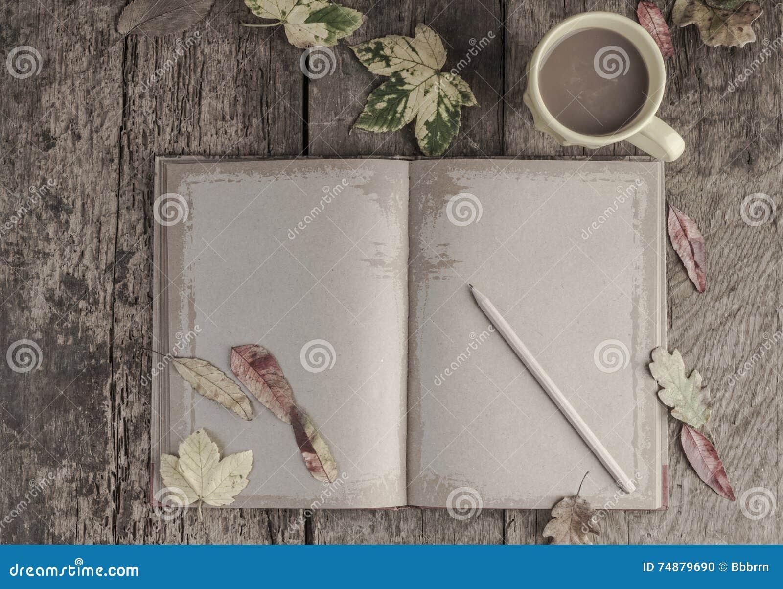 Kaffe och anteckningsboken på trätabellen dekorerade med höstsidor
