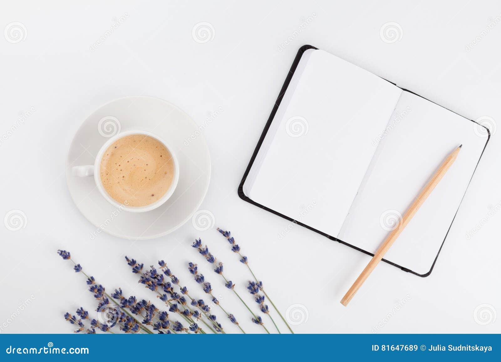 Kaffe, ren anteckningsbok och lavendelblomma på den vita tabellen från över Funktionsdugligt skrivbord för kvinna Hemtrevlig fruk