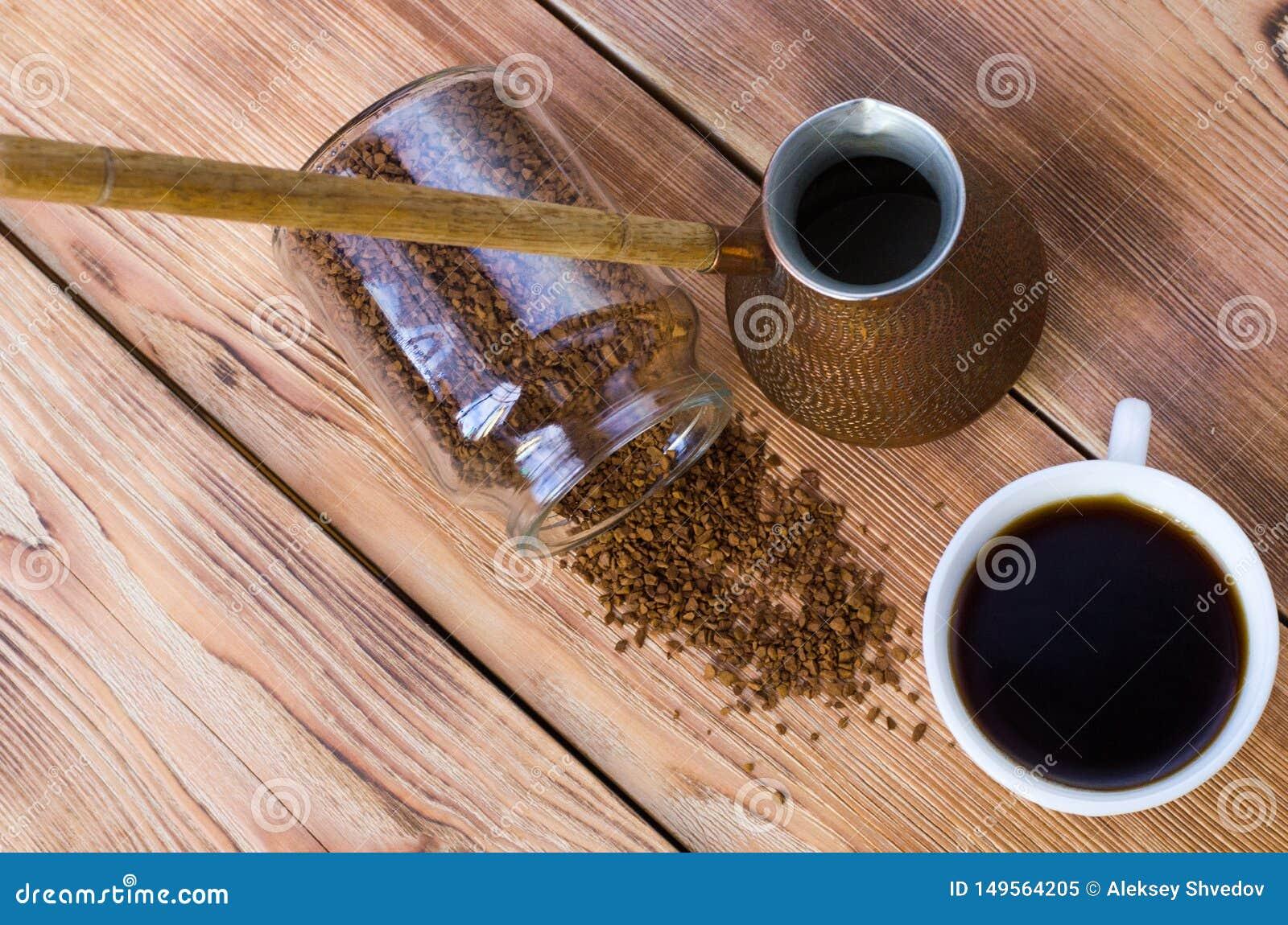 Kaffe st?r bredvid en vit kopp som fylls med varmt kaffe bland spridda kaffeb?nor, tabellen, den b?sta sikten som ?r horisontal