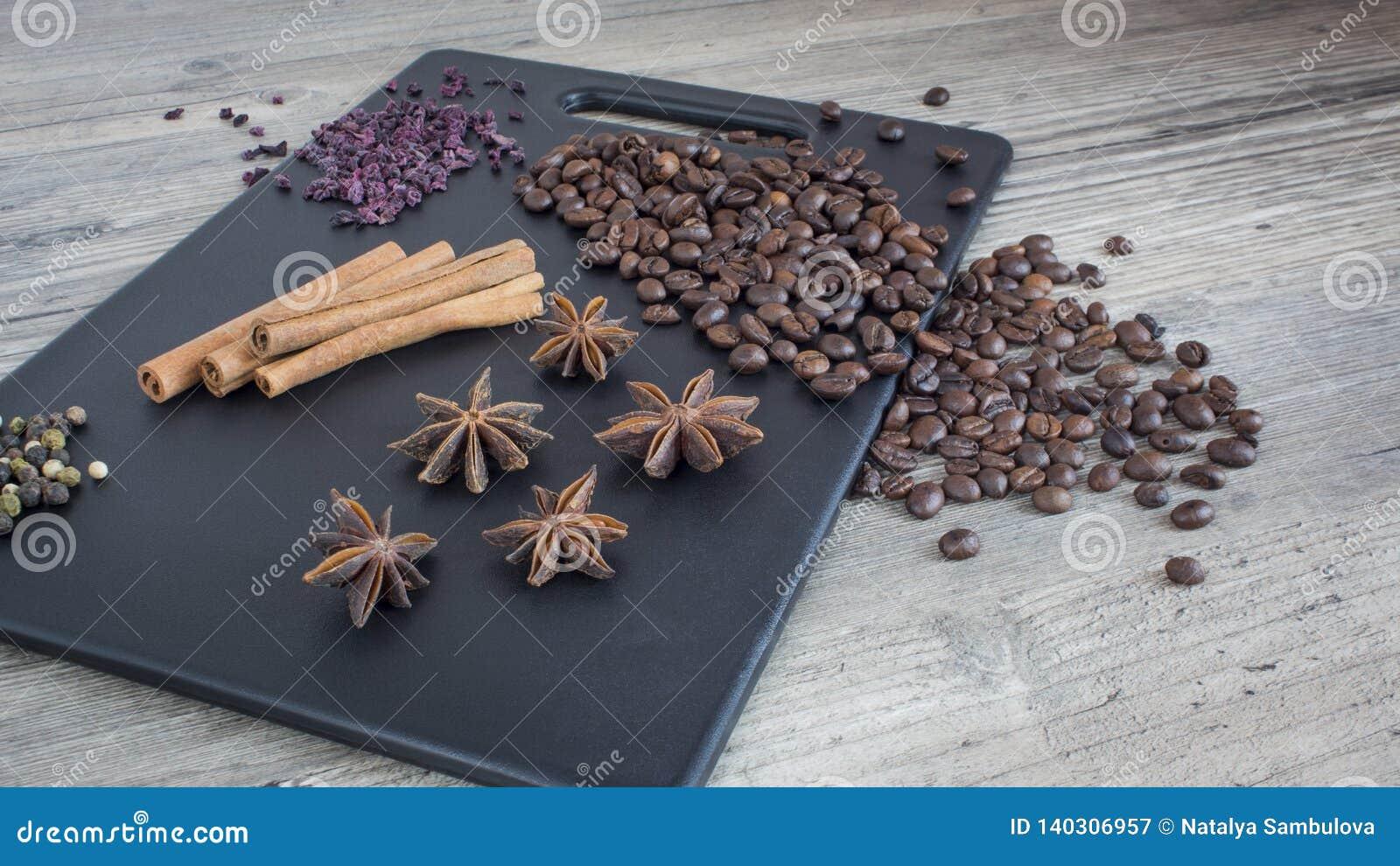 Kaffebönor, kanelbruna pinnar och stjärnaanis Kryddor och mat på trätabellen Ingredienser för framställning av kaffe