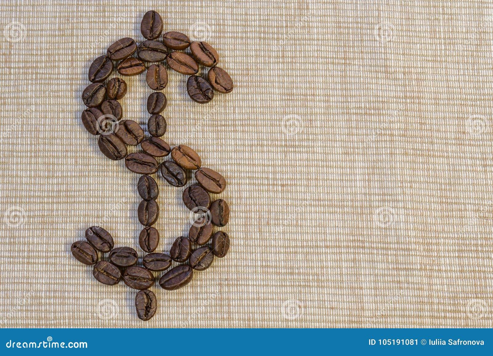 Kaffebönor läggas ut i form av ett dollartecken på en beig