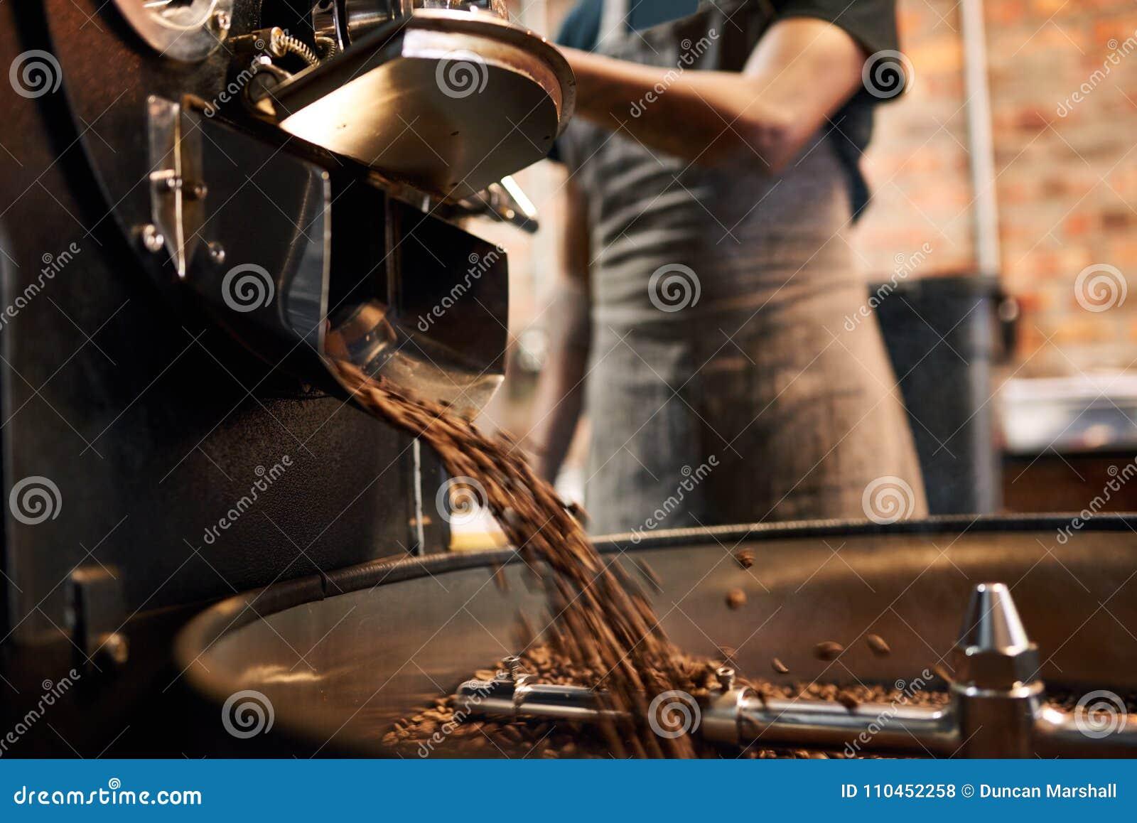 Kaffebönor som hälls ut ur en stekhet maskin för kaffe
