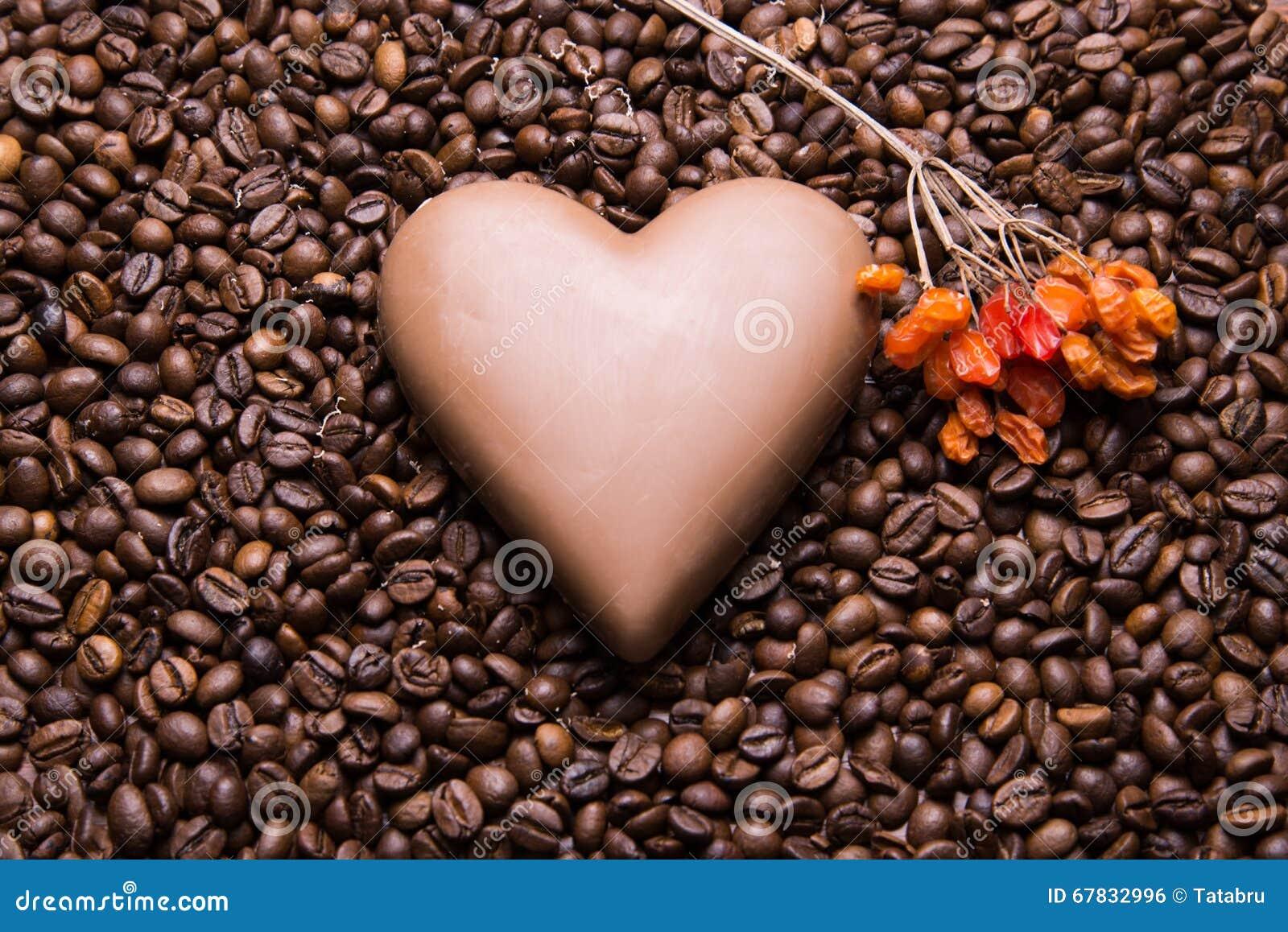 Kaffebönor tapetserar med chokladhjärta och viburnumberrie